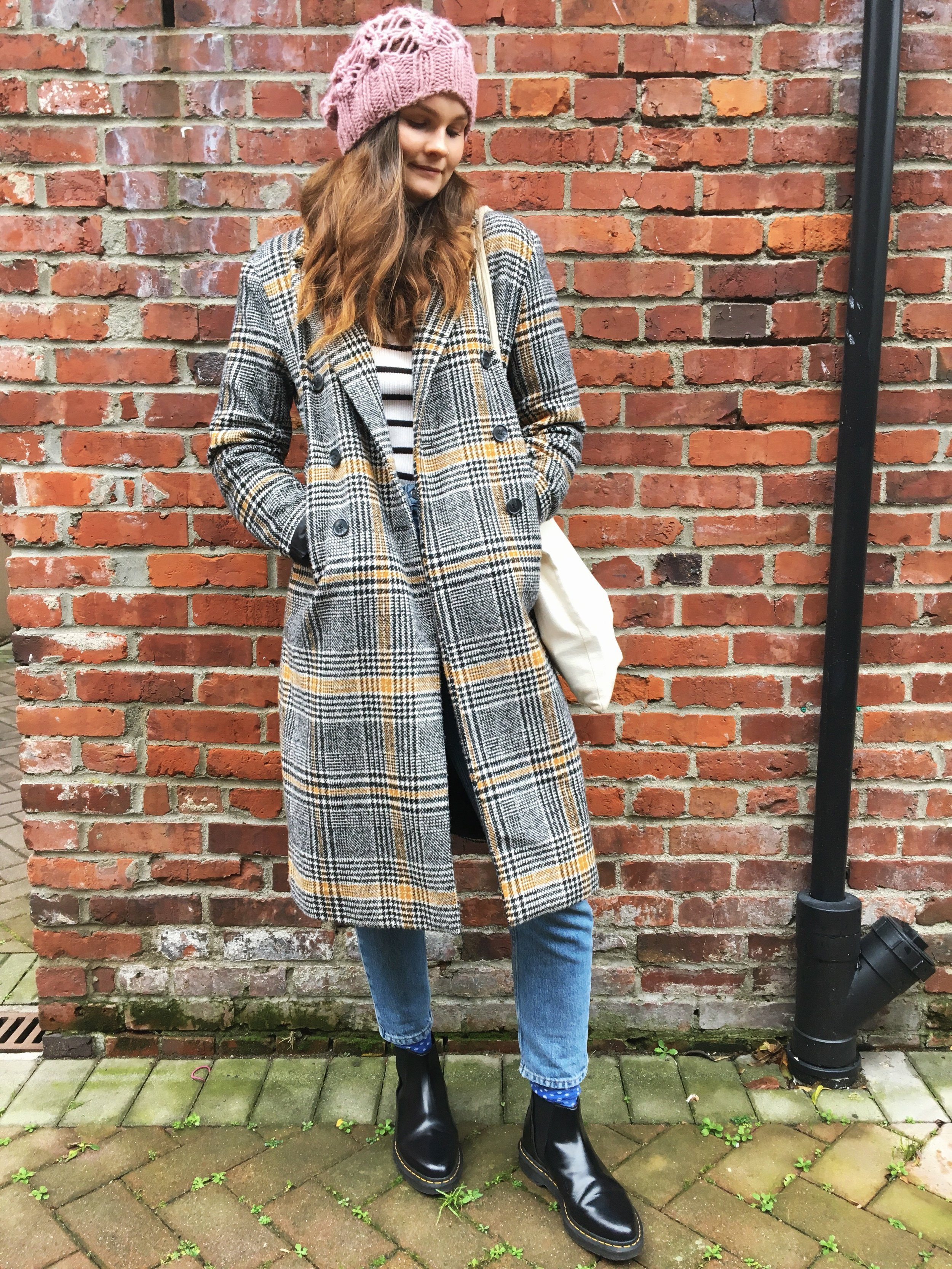 woman standing against brick wall wearing a pink knit toque a plaid coat striped turtle neck topshop mom jeans and doc marten boots lifestyle blogger canadian blogger