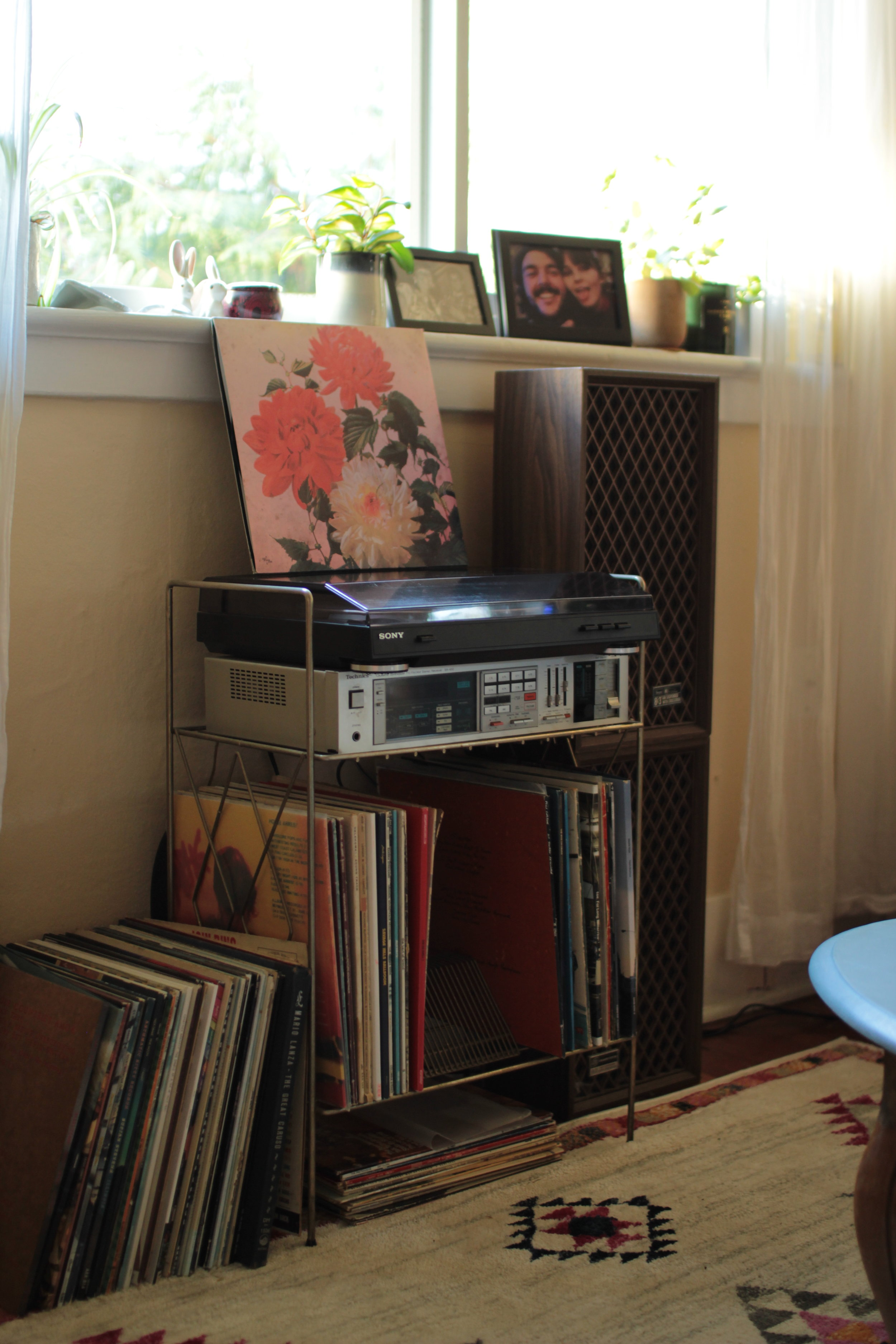 a record player sitting on a record stand with a stack of vinyl beside it The States of Georgia small spaces small apartment survival lifestyle Canadian blog