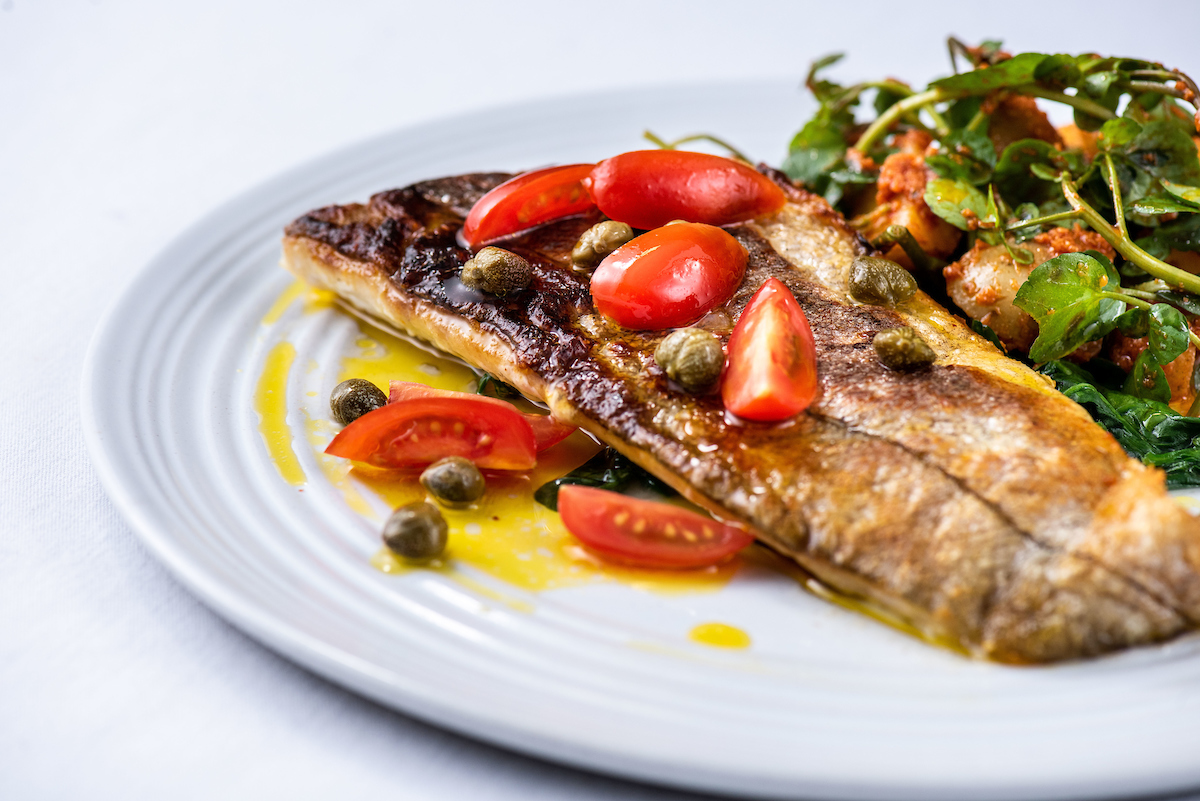 Smoked Haddock with red pesto potatoes and a tomato and caper vinaigrette