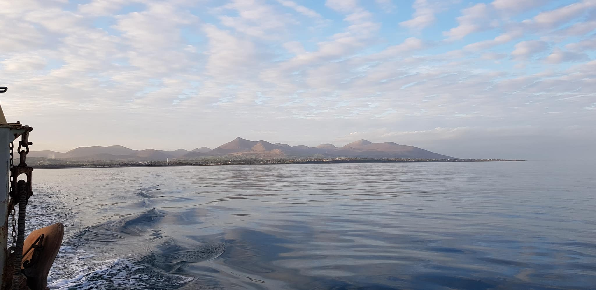 A calm day at sea with the Mourne Mountains glowing by Stanley Hanna