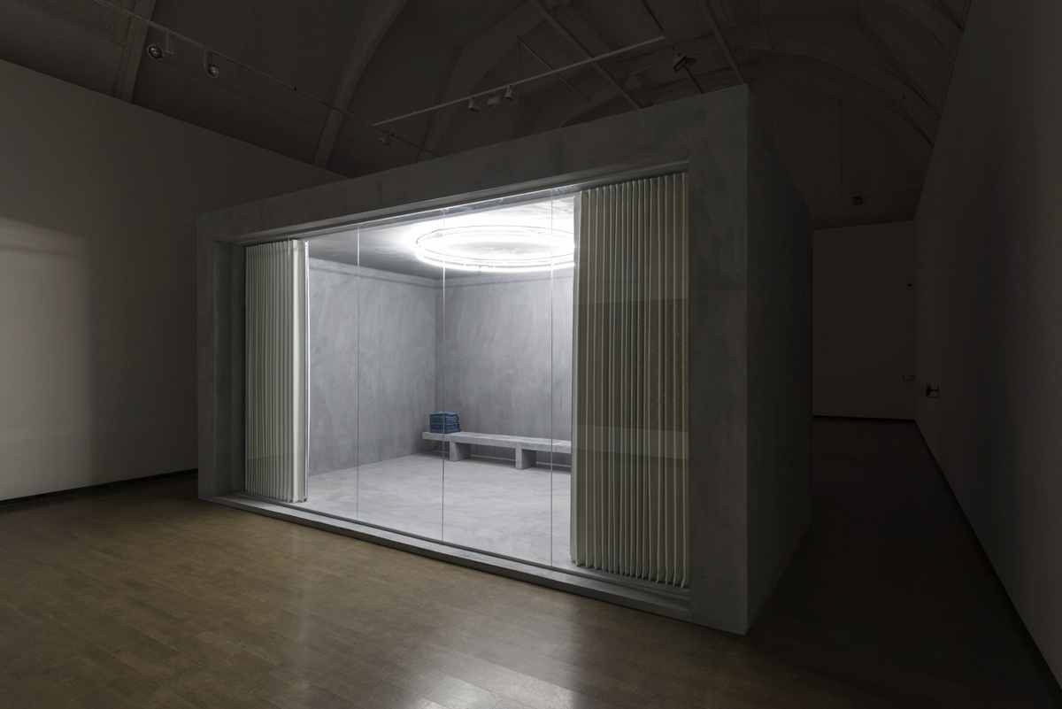 MULTIFAITH , 2015  Béton Ciré render, fabric concertina partition, wood, glass, neon, plywood, prayer mats  600 x 400 x 300 cm