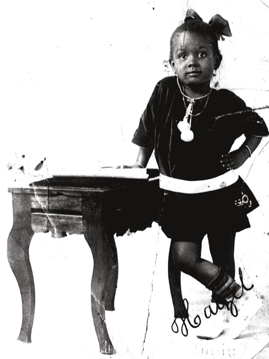 Image Source Unknown. Young Hazel Scott poses by a piano.