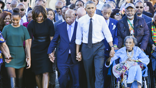 Amelia Boynton Robinson (in blue) holds the hand of President Obama crossing the Edmund Pettus Bridge in 2015, 50 years after she was beaten unconscious. Image Source: The Selma Times Journal