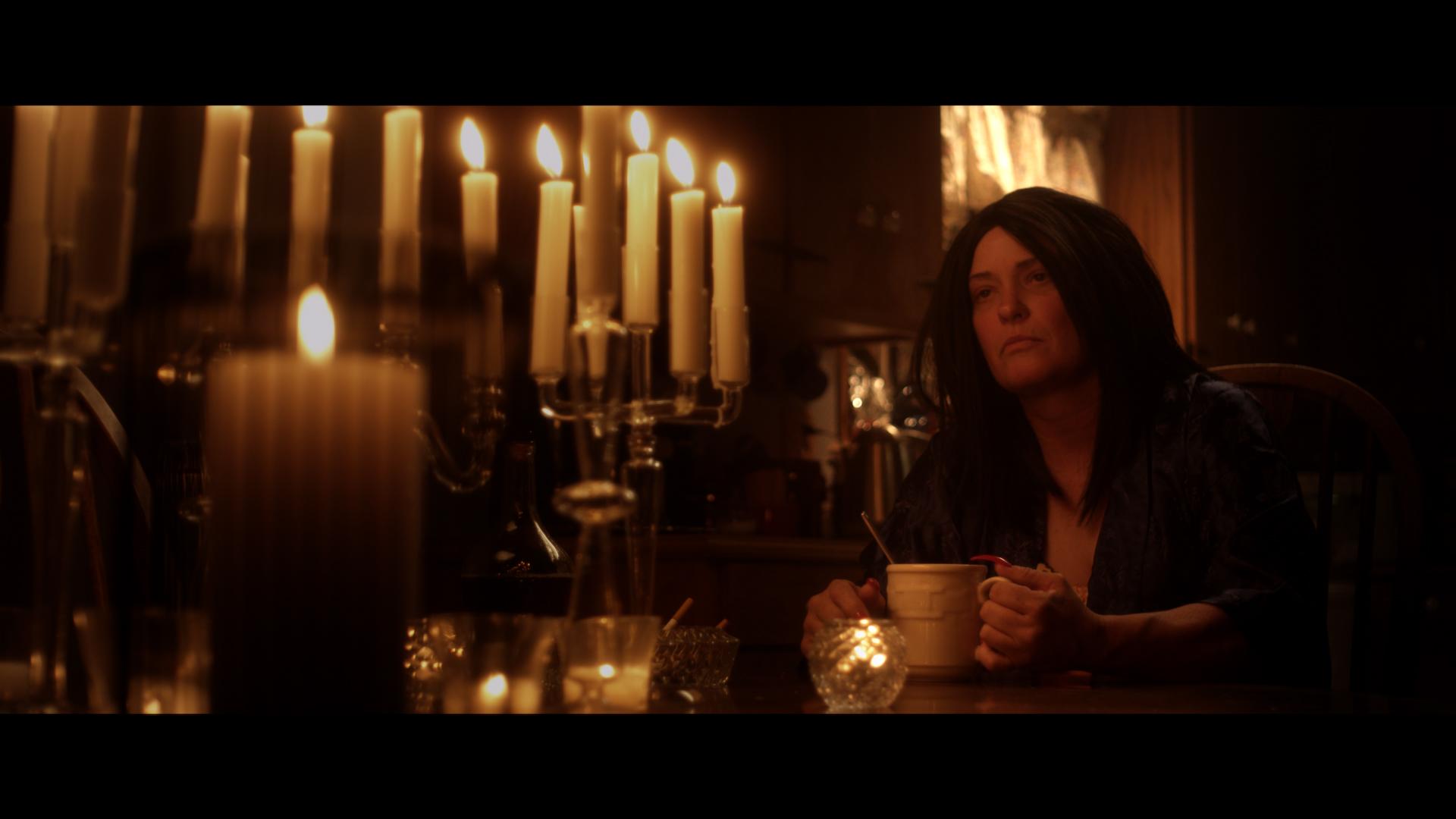 Morian holding mug at candlelit table, reminiscing.jpg
