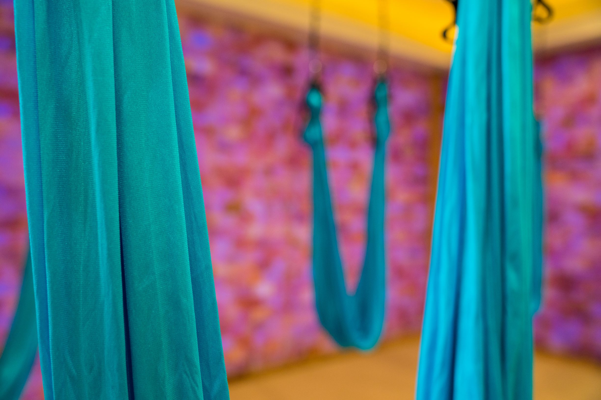 One of our favorite offerings at Pineapple Life is our series of Pineapple Flight classes, also known as Aerial Yoga. This class, in a non-heated room, was designed for all levels. Rest assured that our aerial silks have been tested to accommodate up to 1,000 pounds (not that they need to). Register early for these classes as they fill quickly!  Aerial Yoga offers a multitude of benefits to the body. Providing the opportunity for deeper stretches, longer inversions as well as an amazing way to attempt and practice hand stands, our Pineapple Flight classes have become one of our most popular yoga programs. Aerial yoga provides so many benefits to the body including (but not limited to) detoxification, improved flexibility, stress relief, back pressure relief, anti-aging and improved focus and memory.   Pineapple Flight:  Deepen your Yoga practice in a playful way while you use the hanging aerial silks. Traditional yoga poses take on a different vibe with the use of Silks and allow you to strengthen, tone, and energize - not to mention, invert and allow gravity to naturally decompress your spine. Give it a try, most likely you will become hooked on flying! All levels welcome. Bring mat and water and no jewelry please.   Chill Flight:  This evening class combines four wonderful elements into one deeply relaxing class that will have you slipping into your evening slumber feeling dreamy and calm. Using aerial silks, candlelight, yoga and meditation will almost guarantee one of the best sleeps you've ever had and who couldn't use that? All levels Welcome. Practiced in room temperature. Bring mat and water and no jewelry please.