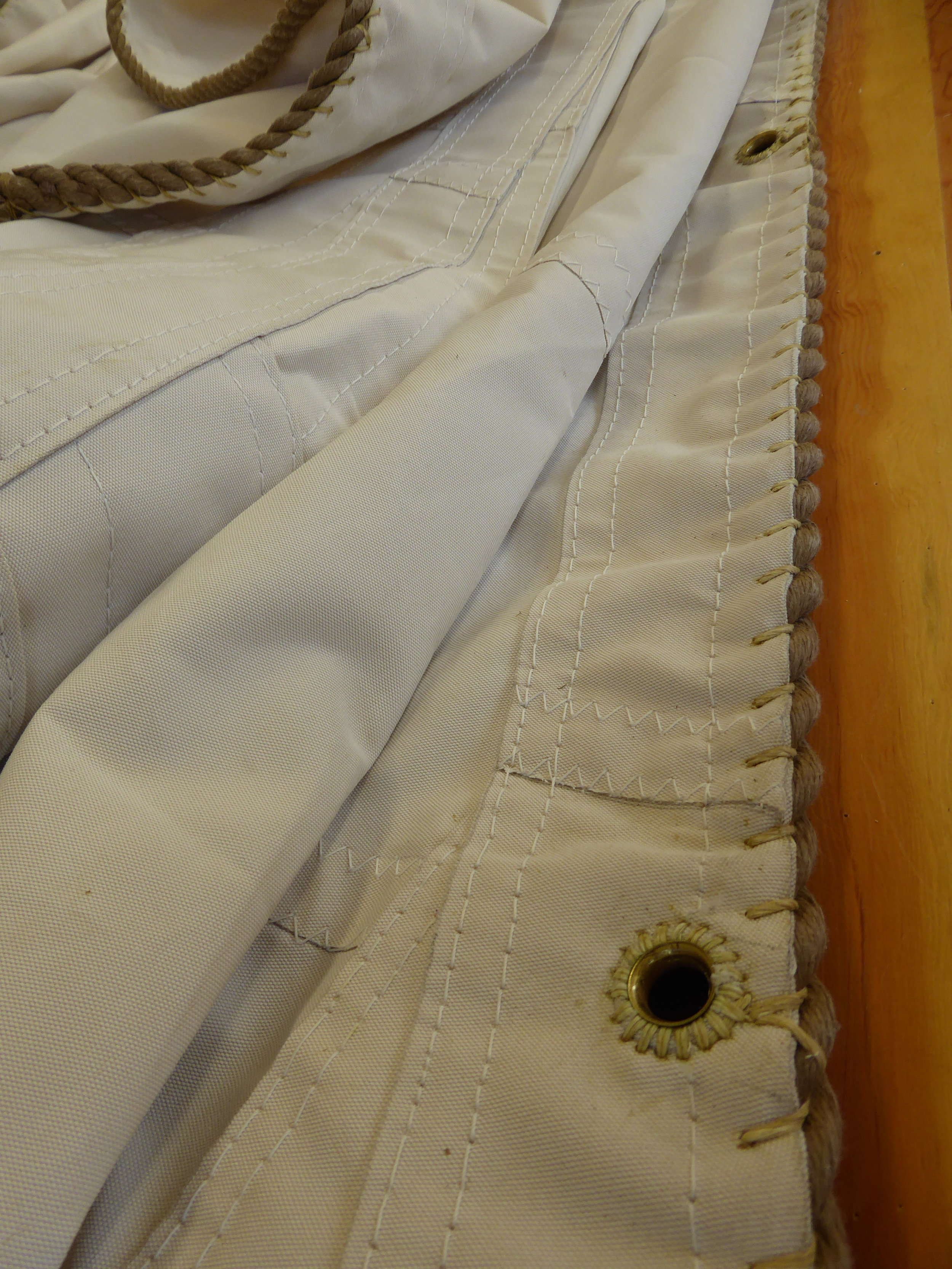 Close-ups of hand sewn foot grommets by Traditional Rigging Co., the maker of Edna Lockwood's new sails.