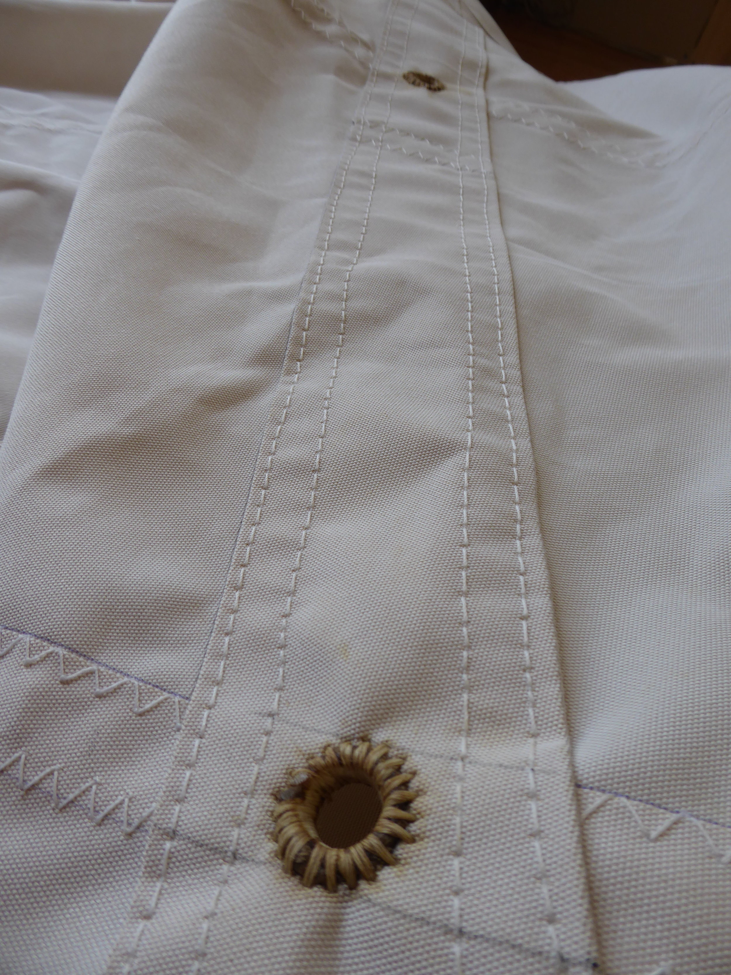 Close-ups of hand sewn reef grommets by Traditional Rigging Co., the maker of Edna Lockwood's new sails.