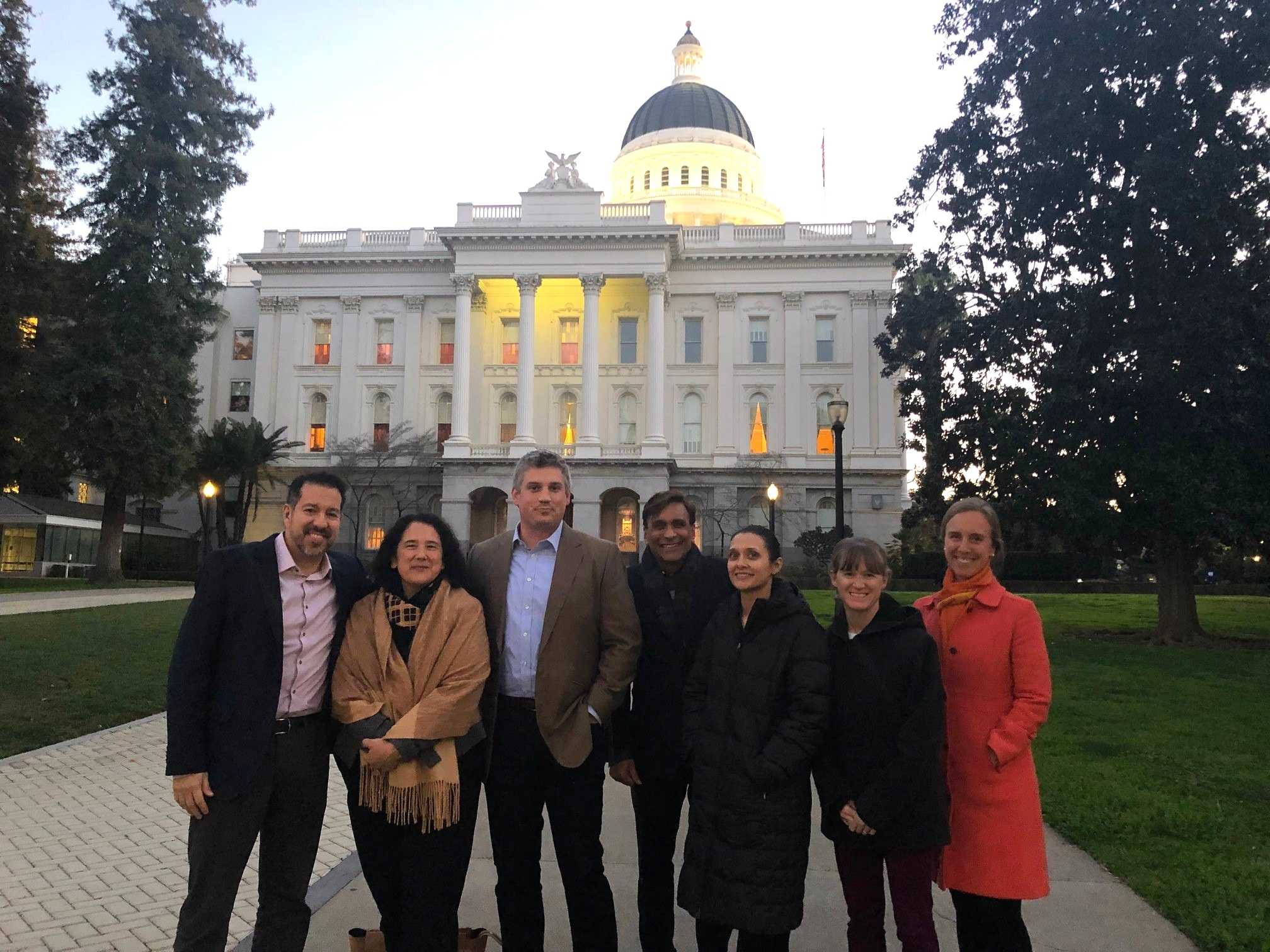 Larta's Carlos Gutierrez (CSO), Isabel Casillas Guzman (Senior Advisor) and Rohit Shukla (CEO) accompanied by representatives from current and alumni companies Blue Forest Conservation, Mango Materials, and 7 Generation Games stand at the entrance of California's capitol in Sacramento.