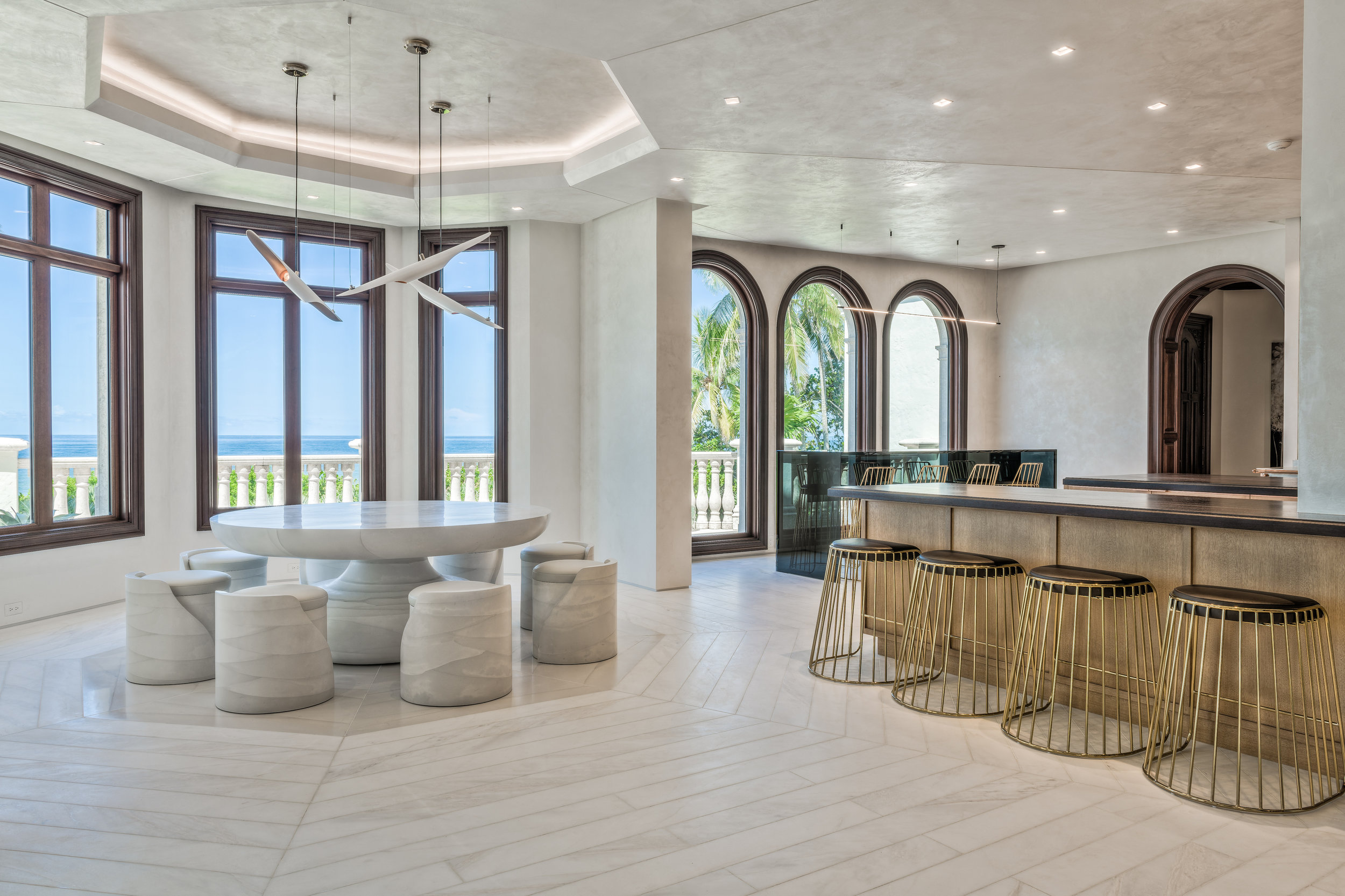 Private Beachfront Estate Kitchen Nook Overlooking a sprawling oceanic view, this room features masterfully inset stone flooring, complex angular ceiling architecture, and artisan applied finishes. The crown jewel of the space is a spectacular cast concrete dining set commissioned by designer Chad Jensen, complimented with a chandelier inspired by birds in flight.