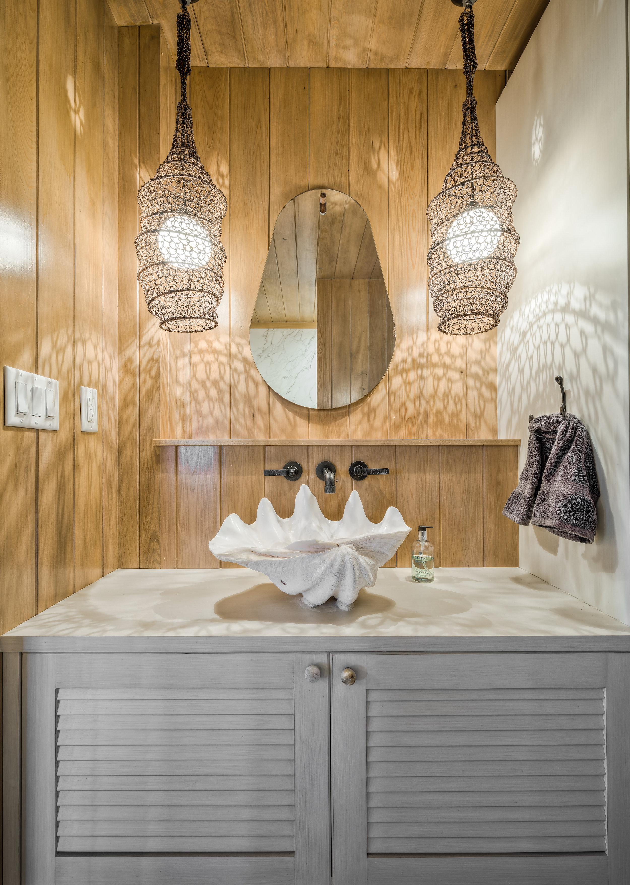 Private Island Beach House Bathroom Authentic giant clam shell sink with custom cabinetry, vintage pipe fittings and fishnet pendant lights