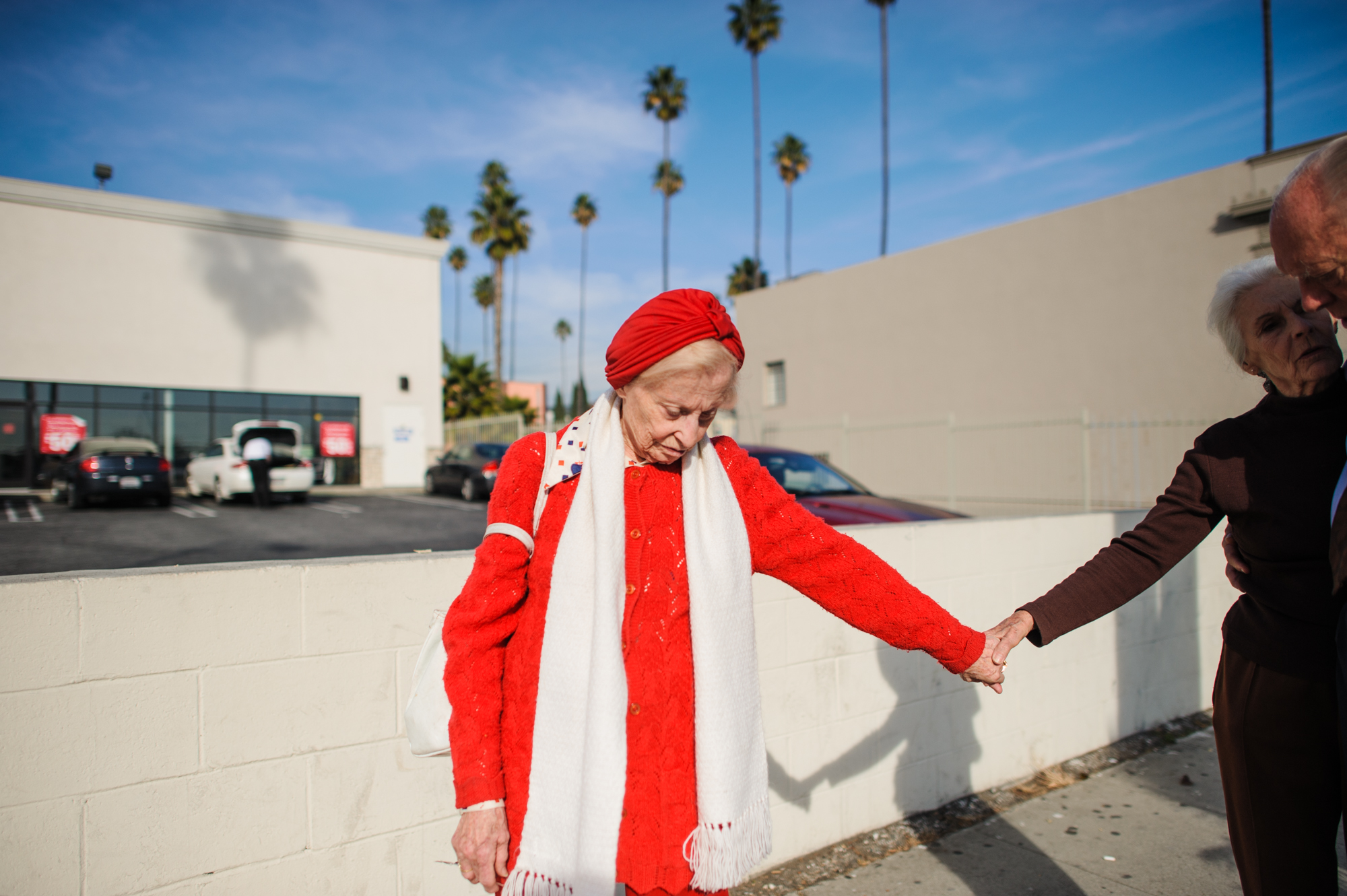 Adina stands on the sidewalk in Los Angeles, as Jeanie holds Adina's hand while having a conversation with Will.