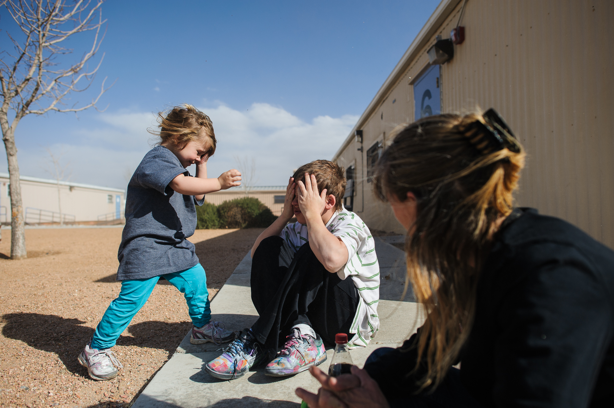 Vinny, age 13, plays a game with his sister, Elycia, age 4, outside the counseling office where he will be evaluated for post traumatic stress, 2012.