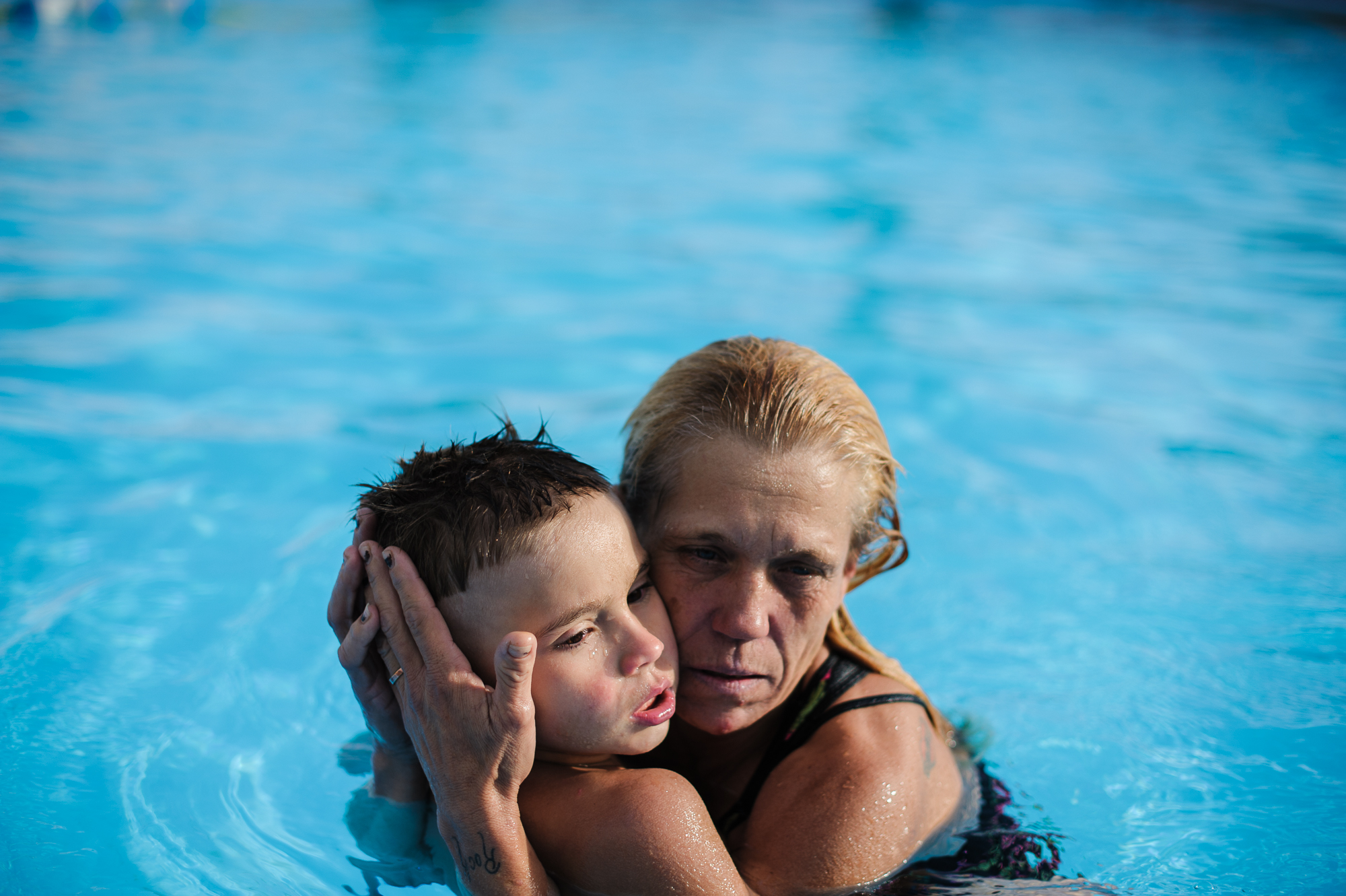 Eve holds her youngest son, Michael, in the pool at the motel, 2013.