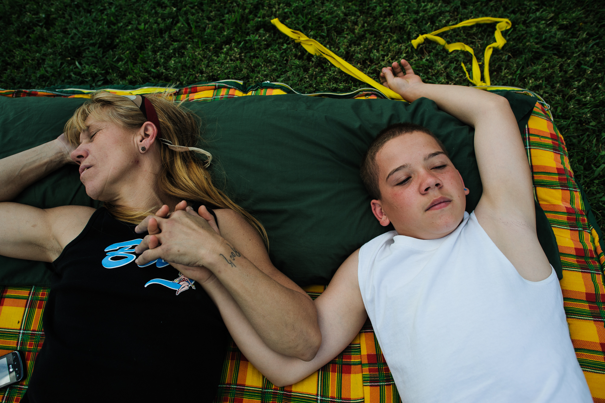 Vinny, age 13, lies on a blanket with his mom, Eve, as she sleeps in the backyard of his aunt's home during an organized family visit, 2012.