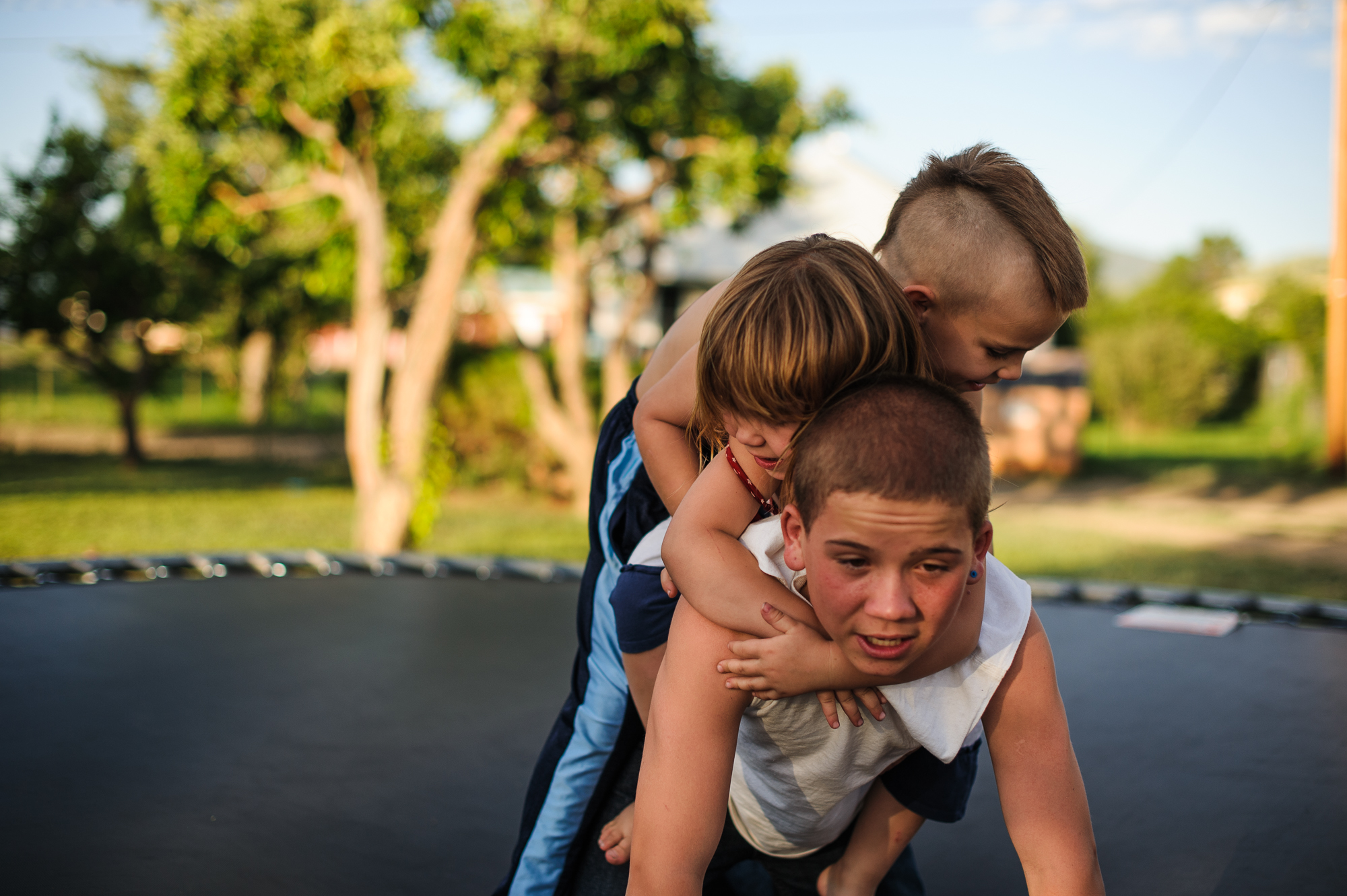 Vinny, age 13, carries his sister and brother on his back on a trampoline at his aunt's home during an organized family visit, 2012.
