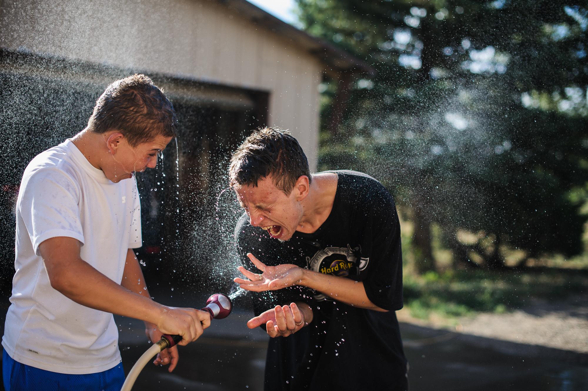Vinny, age 13, sprays David, age 19, with a hose, 2012.