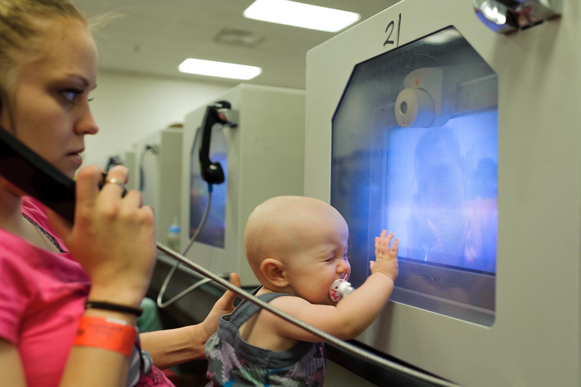 Felicia, age 20, and Lily, age 10 months, see David, age 20, through video visitation at the county jail, 2013.