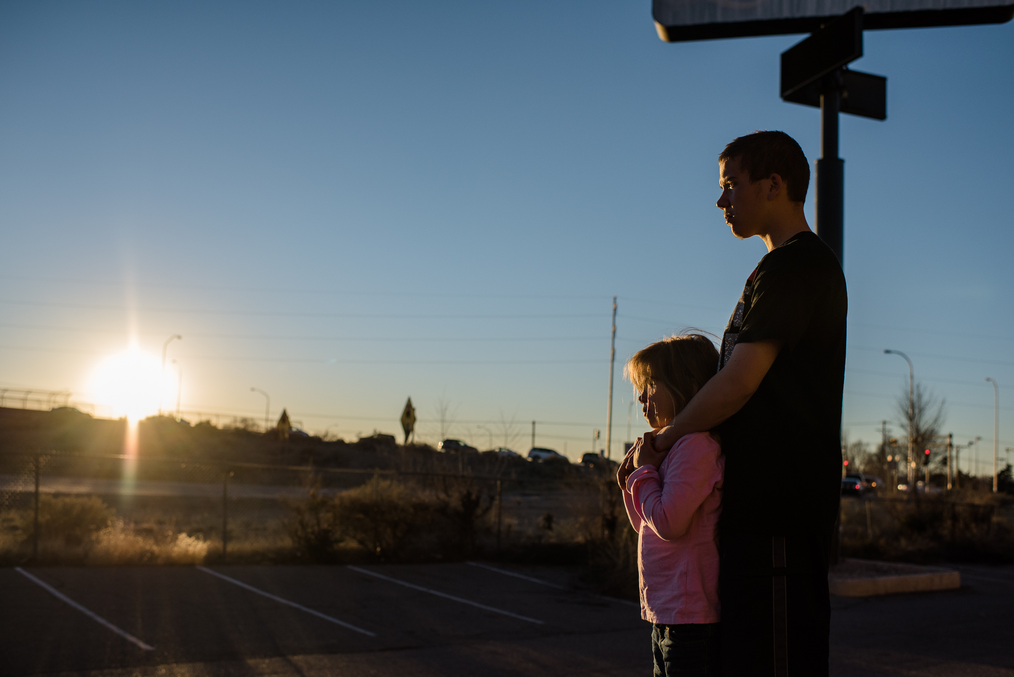 Vinny, age 16, and Elycia, age 7, watch the sunset behind Interstate 40 from the motel parking lot, 2015.