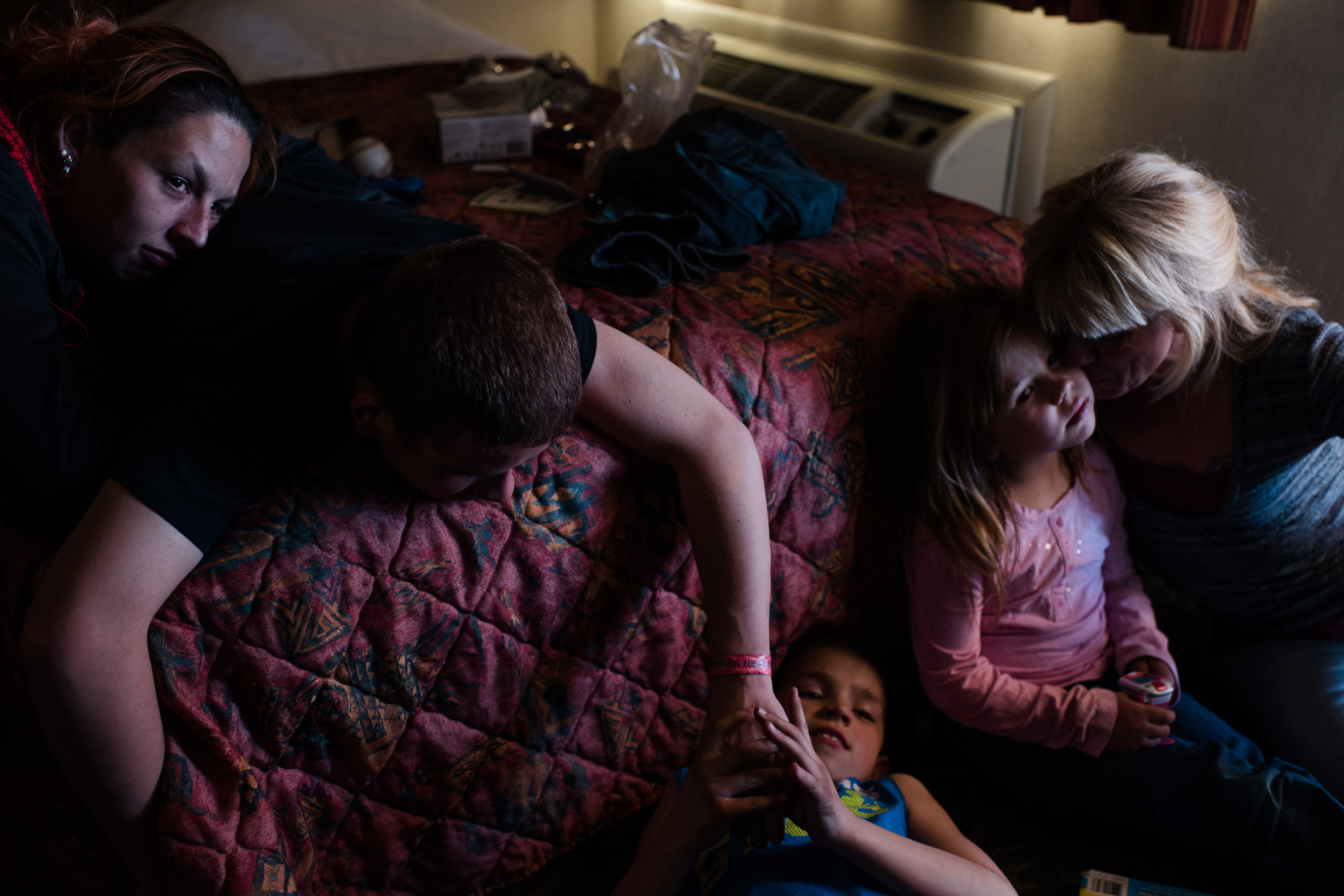 Vinny, age 16, tickles Michael, age 10, while Krystle rests her head on Vinny's back; Eve sits with Elycia on the right side of the bed during a visit at Eddie's motel room where Elycia and Michael live, 2015.