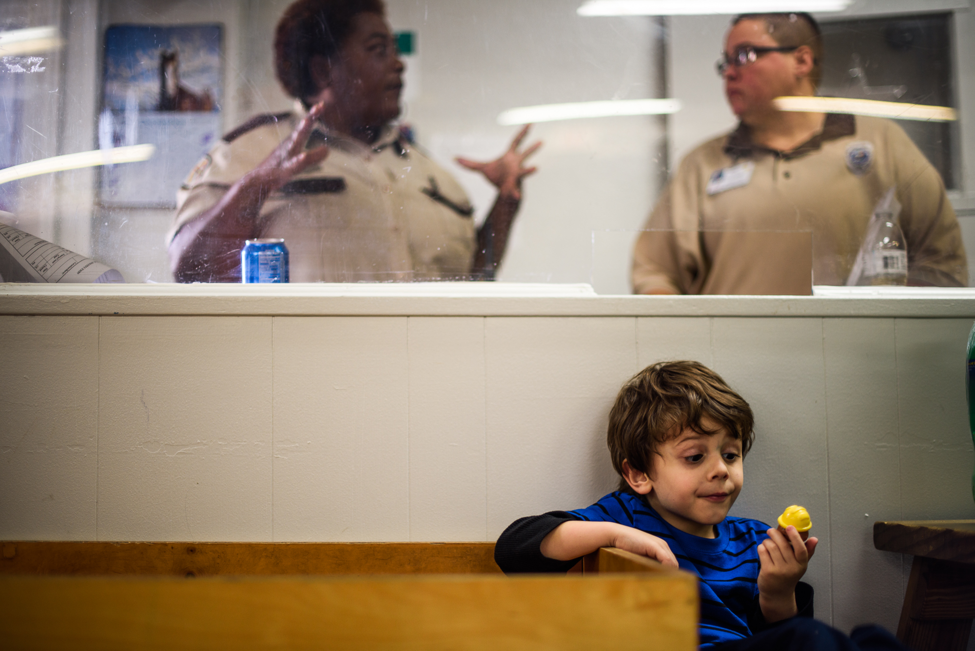 Angel, age 5, looks at a toy as correctional officers communicate behind him during a visit with his mother, Mary, at the Hernando Correctional Facility in Brooksville, Florida.