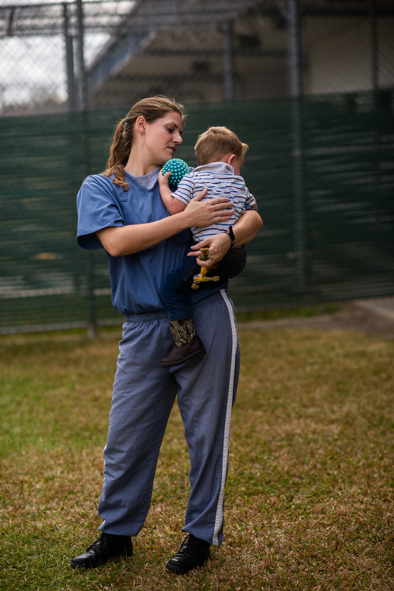"Jessie, age 23, holds her son, age 2, during a bonding visit at the Lowell Correctional Institution in Ocala, Florida. Jessie is incarcerated for 4 years for bringing controlled substances to her boyfriend during a prison visit. ""Sometimes you just want love. And you're willing to do whatever you can to get it,"" she shares."