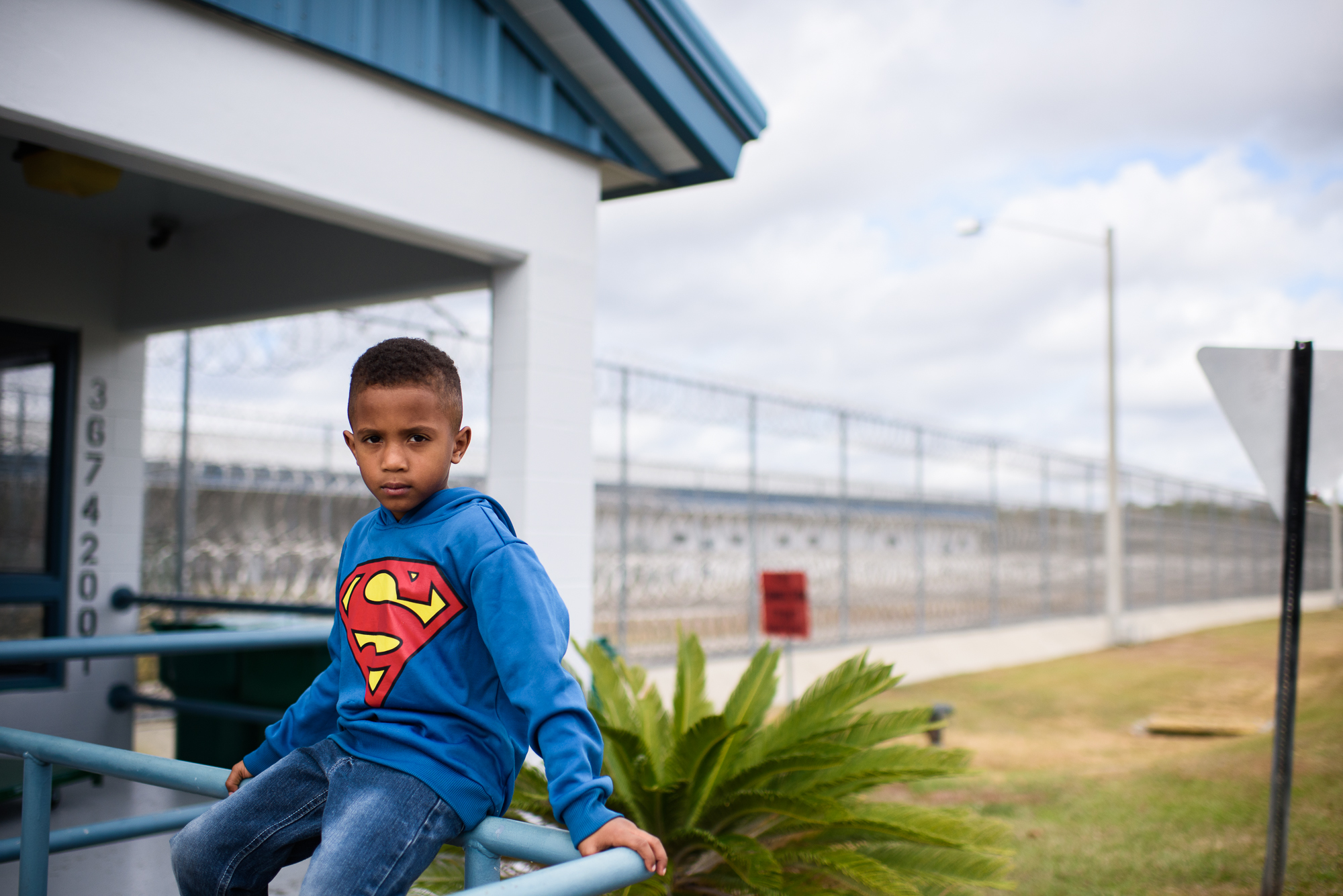 A boy sits outside the entrance of Lowell Correctional Institution in Ocala, Florida before visiting his mom.