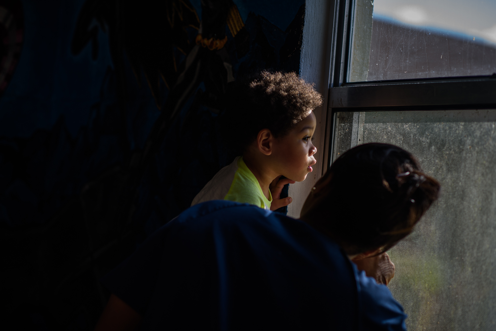 A boy looks out the window with his grandmother at the Homestead Correctional Institution.