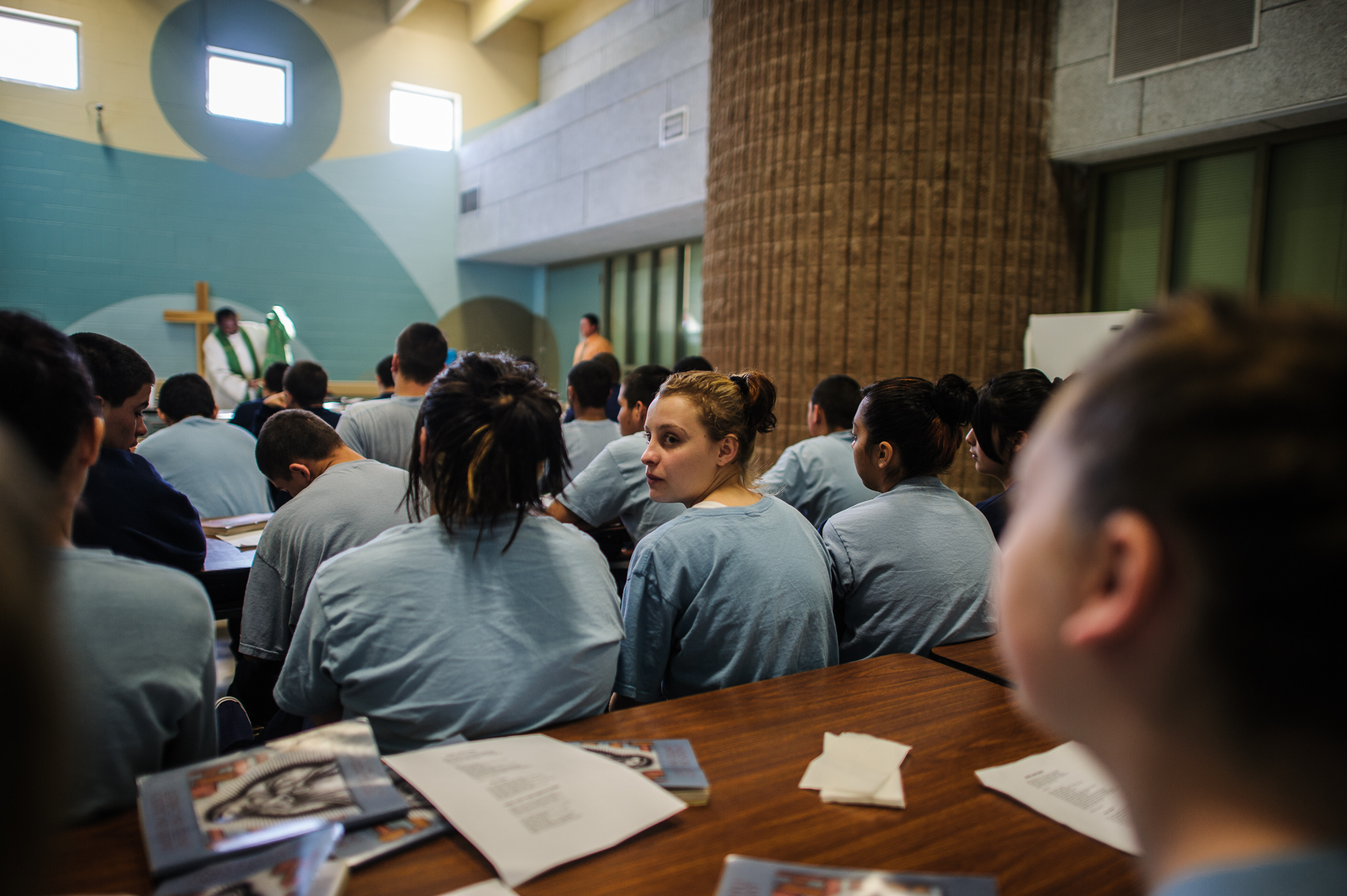 Alysia, age 16, looks back as she sits amongst youth during a Catholic Mass on Sunday at the juvenile detention center.