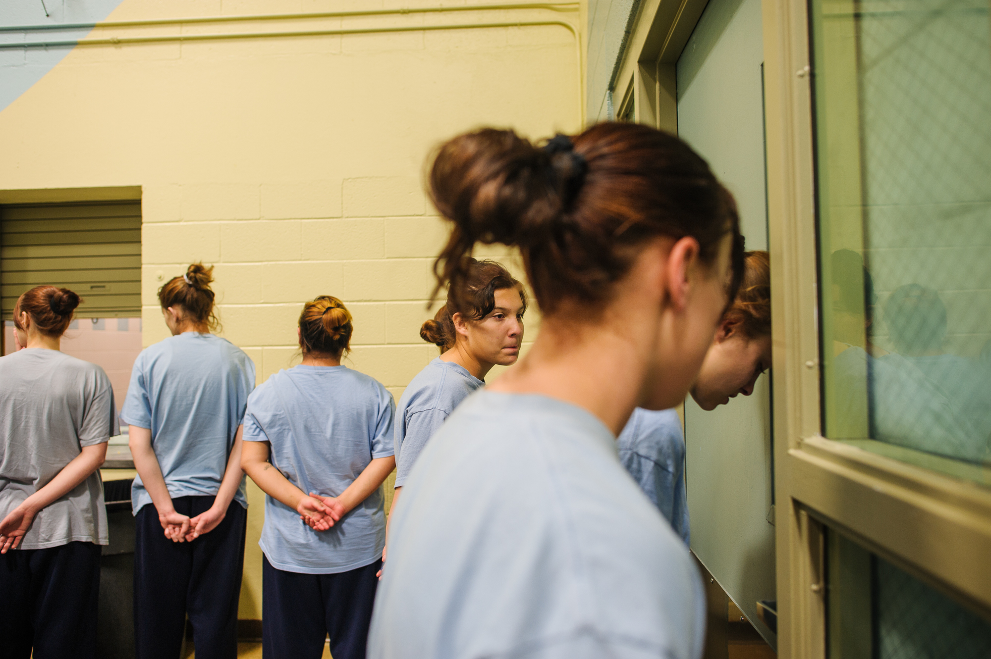 Alysia, age 16, leans her head against a door as she stands in line with other girls in the cafeteria of the juvenile detention center in Albuquerque, NM.