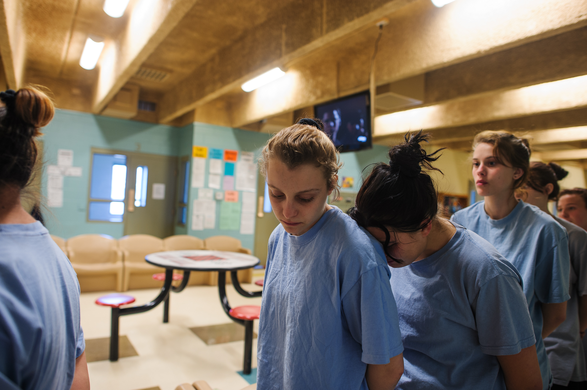 Alysia, age 16, stands in command call, or a line, to exit the girls' unit, while Jasmine, age 15, leans and cries into Alysia's back.