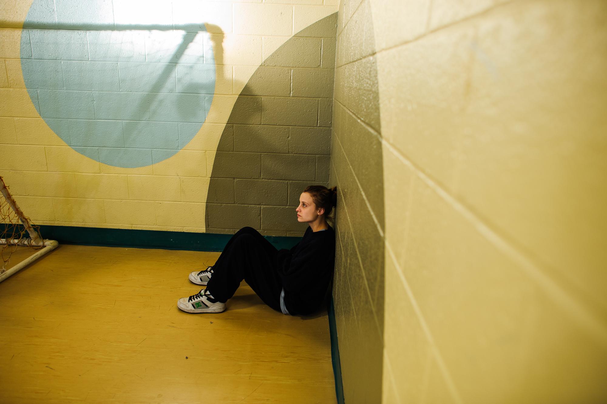 Alysia, age 16, sits inside the gym, as other girls play handball and basketball.