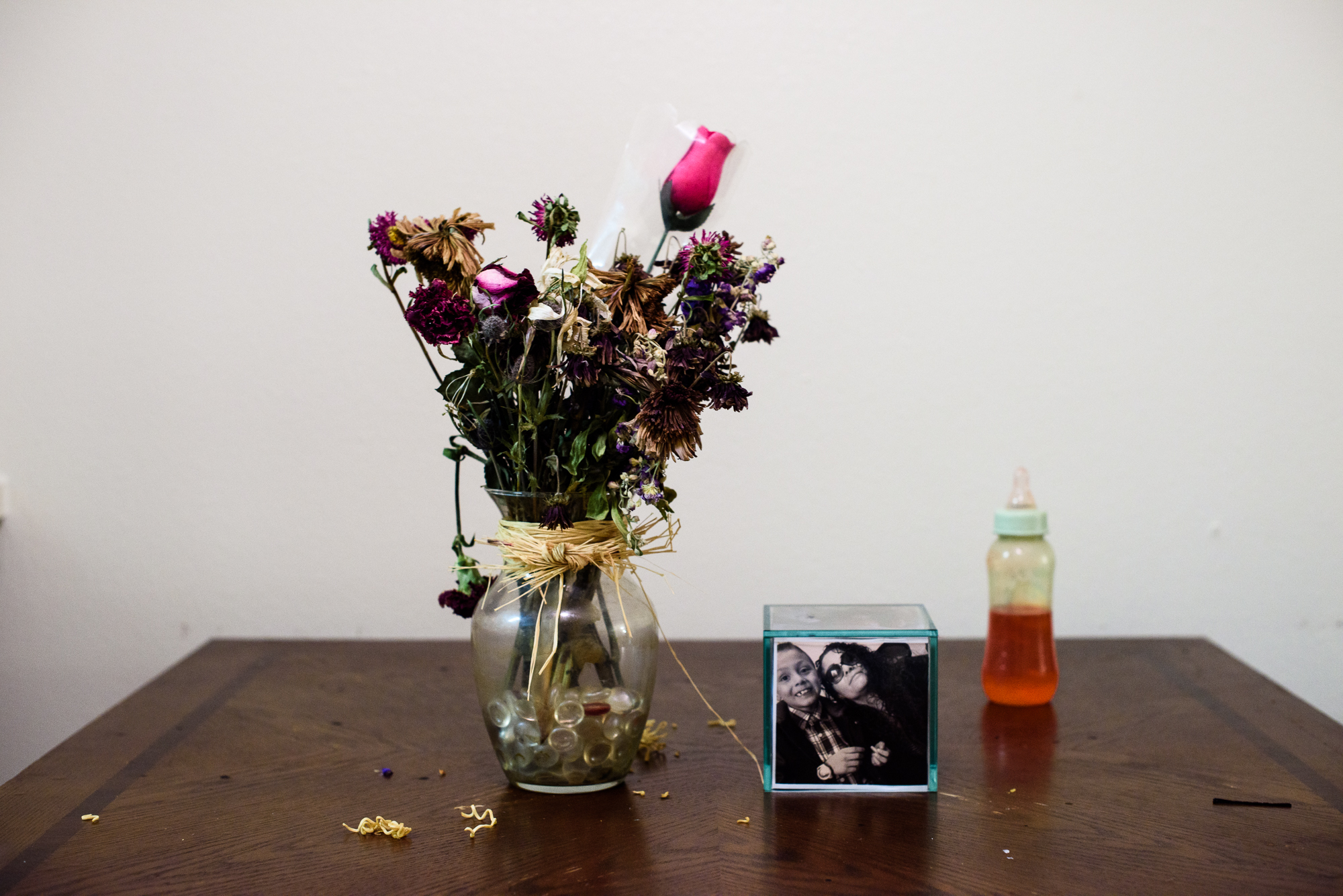 A vase of flowers, a baby bottle, and a picture of Alysia's mom and her brother who is child protective services sits on Alysia's dining room table.