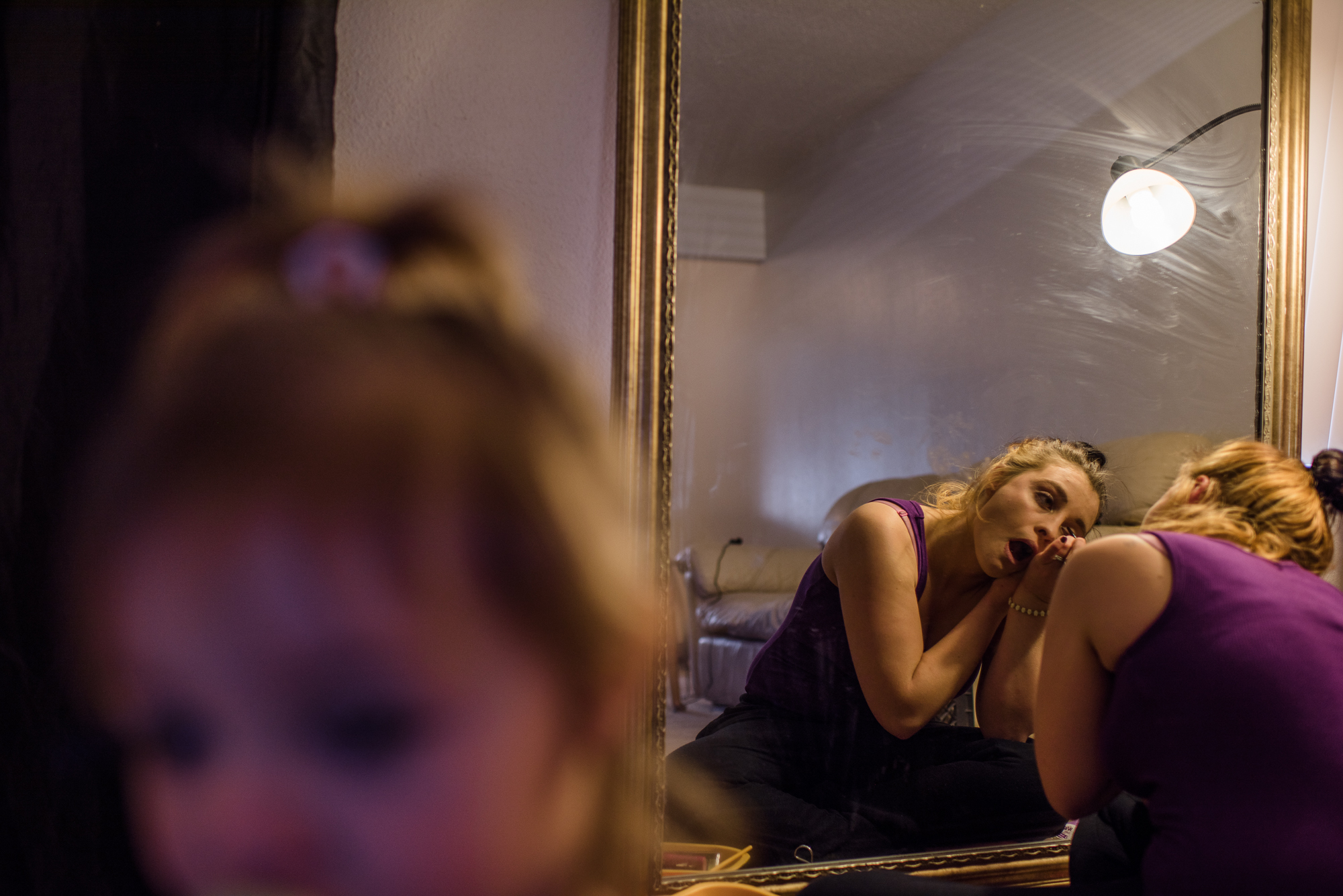 Alysia, age 20, puts on makeup in the morning, as her daughter, Leticia, stands beside her.