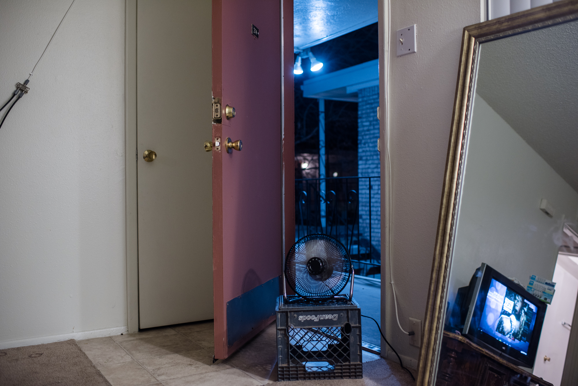 A fan and open door on a summer day at Alysia's apartment,