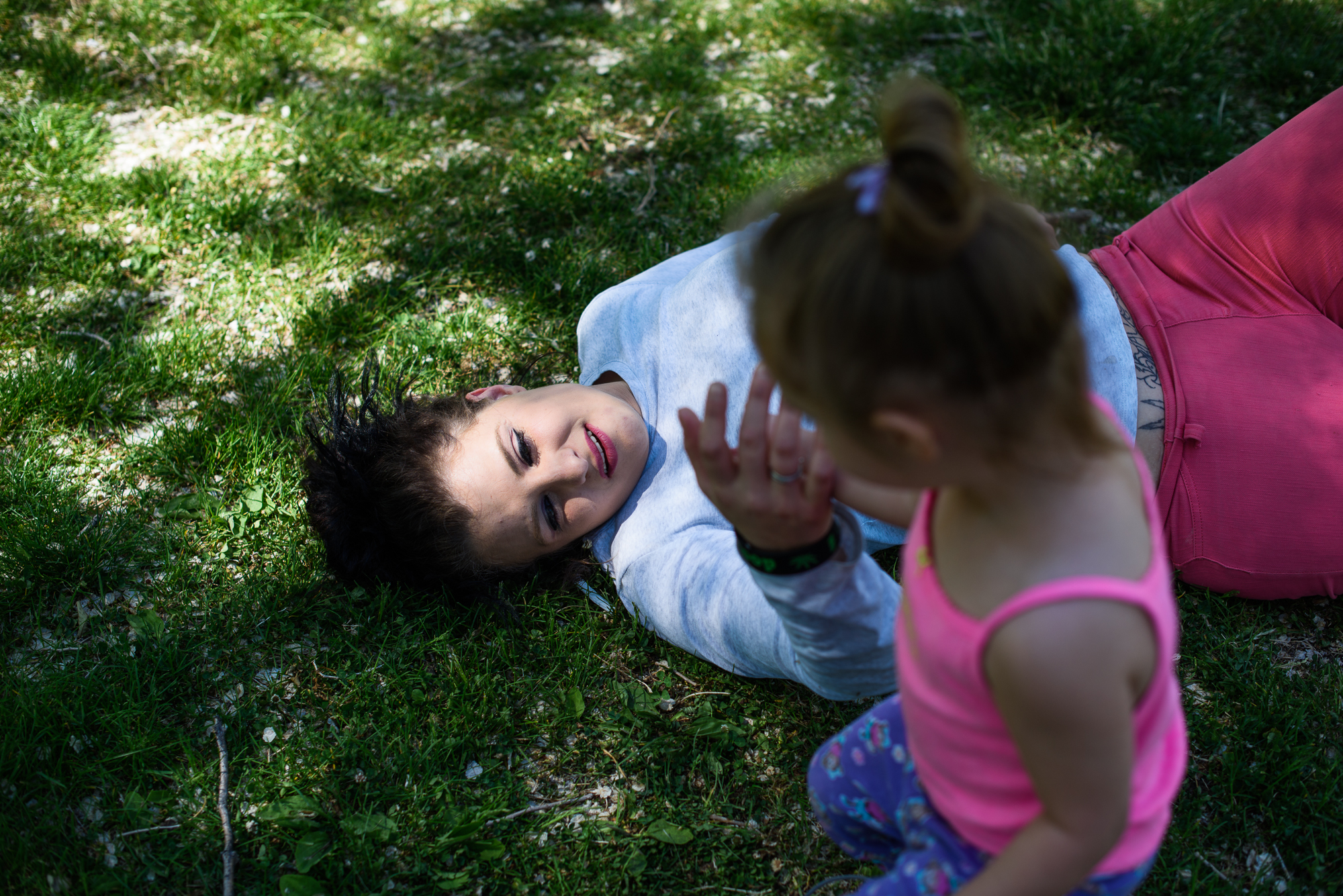 """Alysia lies on grass at the park as Leticia touches her hand. """"I try to give her what I did not have. Take her out. Make childhood something fun and innocent,"""" says Alysia."""