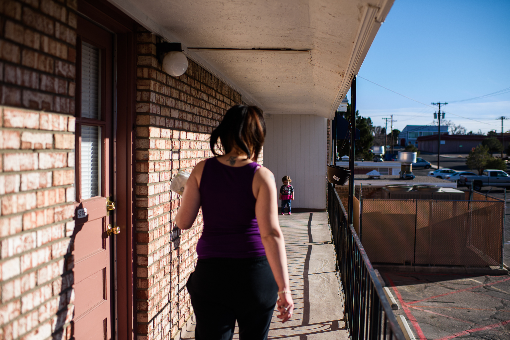 Leticia, age 2, waits for Alysia, age 20, at the end of the corridor, as Alysia walks towards her at their apartment complex.