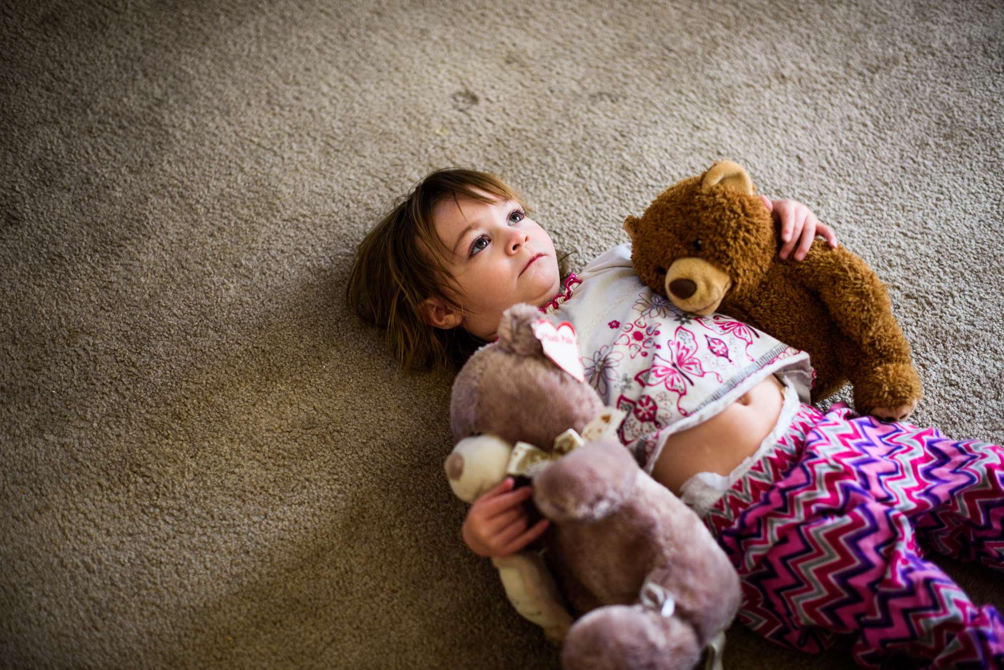 Leticia, age 2, lies on her back and holds two teddy bears.