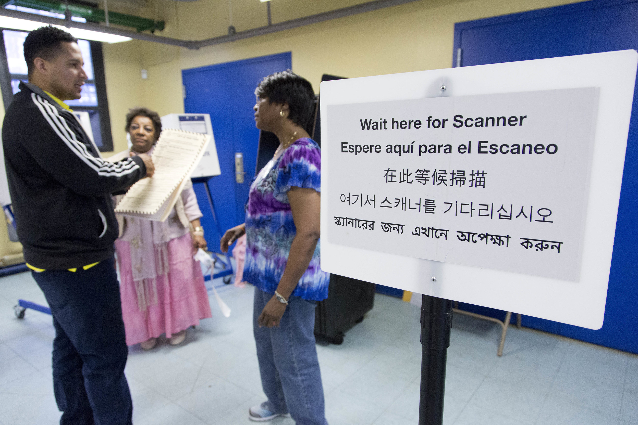 Darling Diaz, left, talks with poll worker Jamie Williams-Rivera before voting in Flushing. Photo by Mark Lennihan courtesy of AP