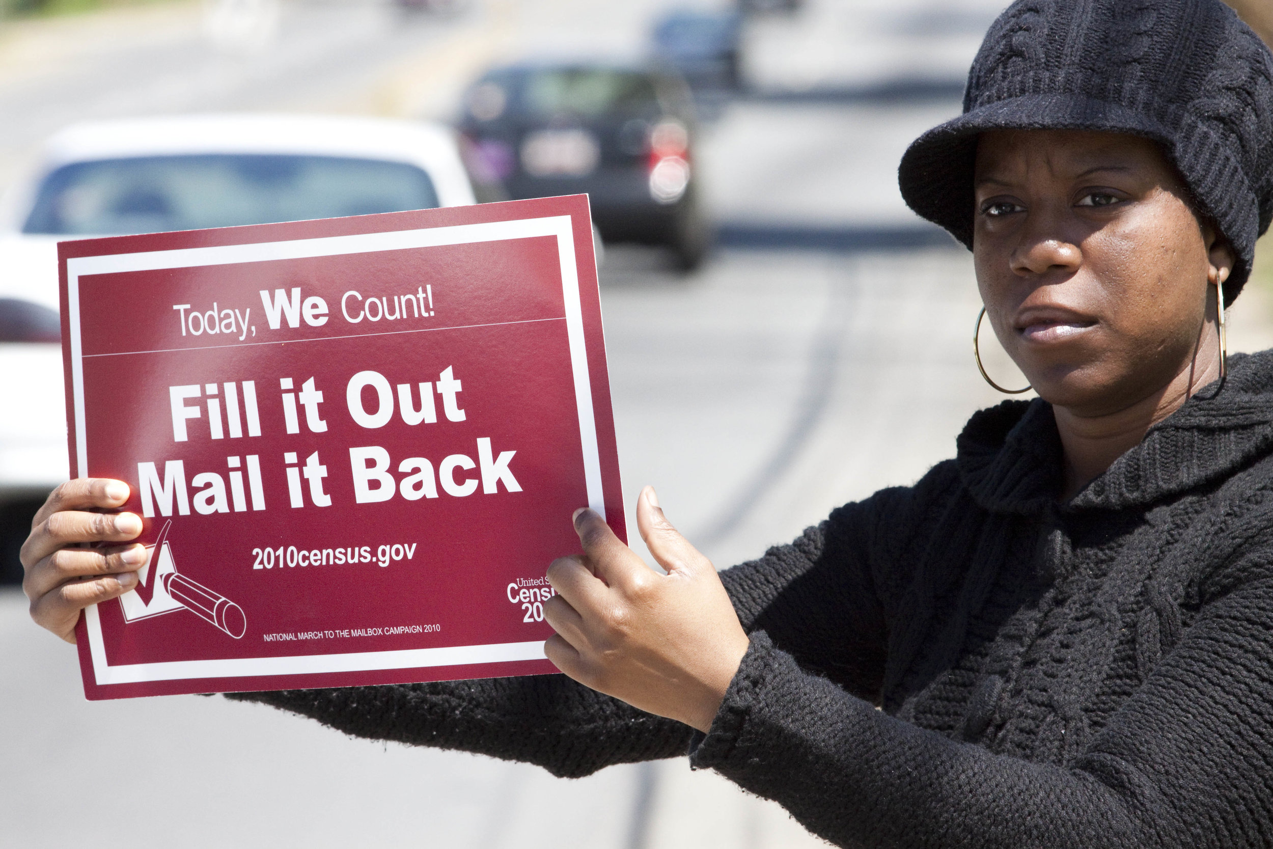 Shanda Burrell, 32, holds a sign encouraging people to complete their 2010 census. AP photo by Jason E. Miczek