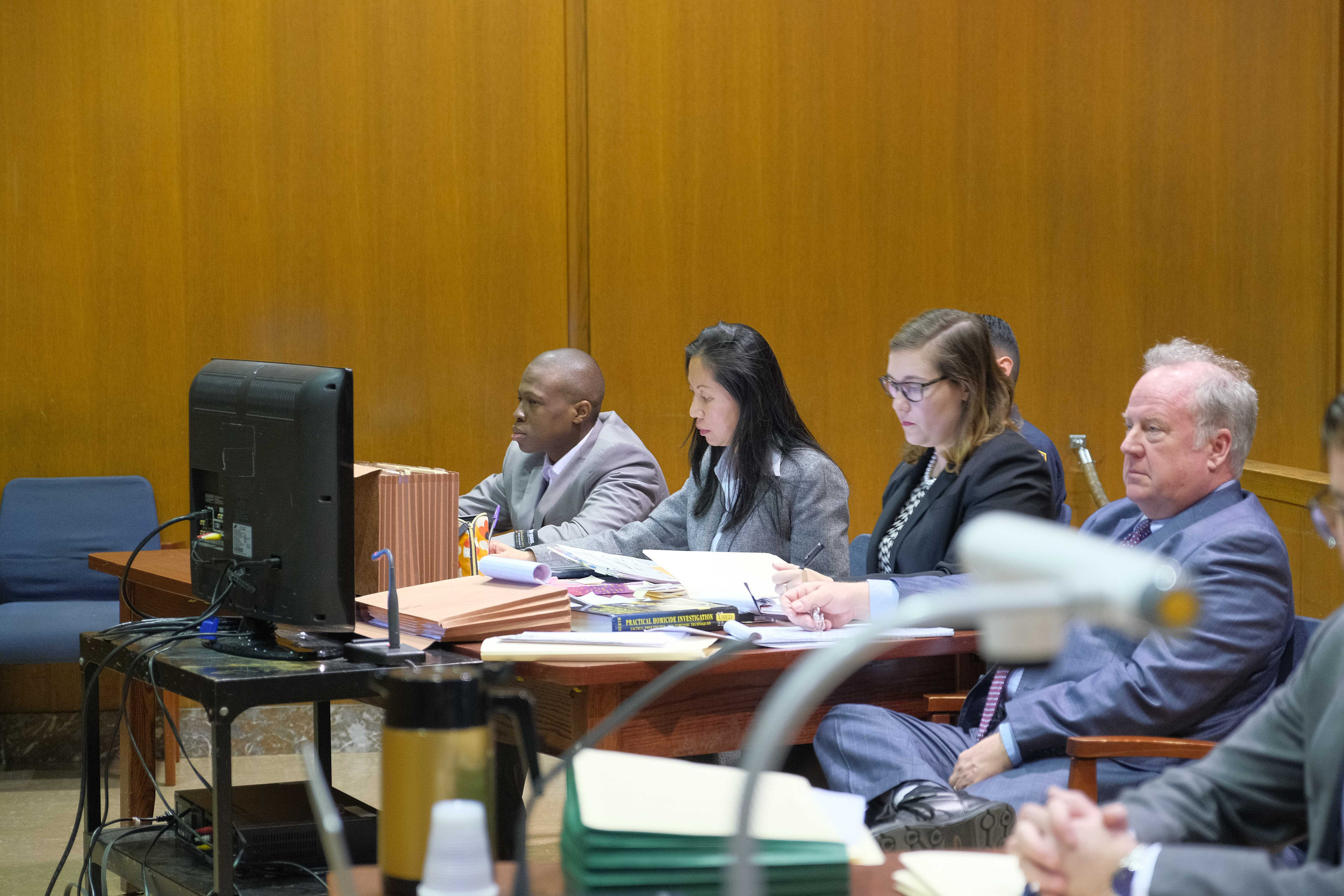 Chanel Lewis (far left) on trial for the murder of Karina Vetrano. Lewis is seated with defense team Jenny Cheung (middle left), Julia Burke (middle right) and Robert Moeller (right). Pool photo by Curtis Means.