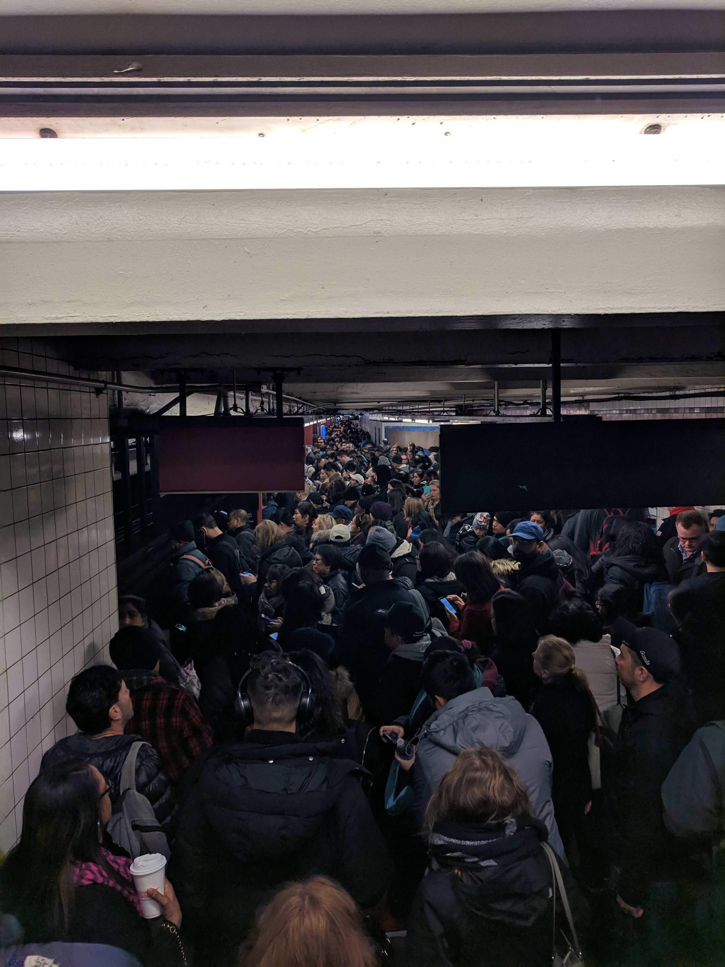Commuters attempt to get to the E train platform at Court Square in Long Island City. Photos courtesy of Euoi.