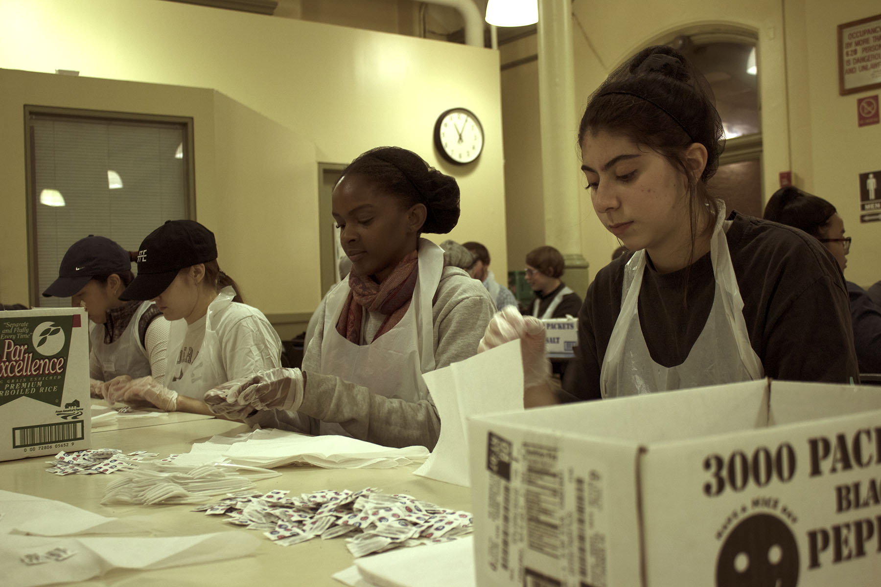 Students from FIT roll silverware into napkins, partly fulfilling a school community service requirement.  Eagle  photos by Victoria Merlino.