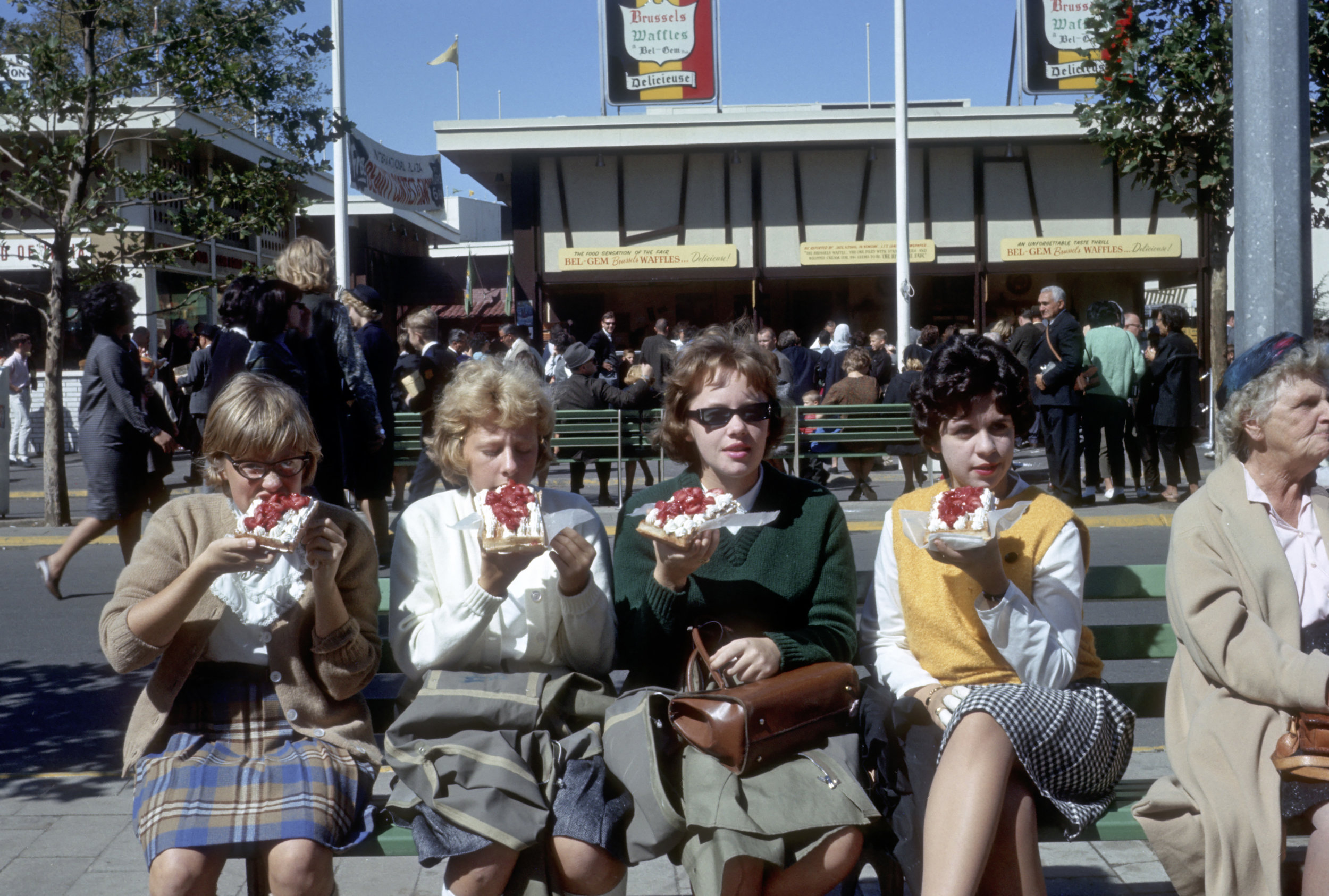 Four young women eat Belgian waffles near the State Pavilion at the 1964 World's Fair. // Photo courtesy of QEDC