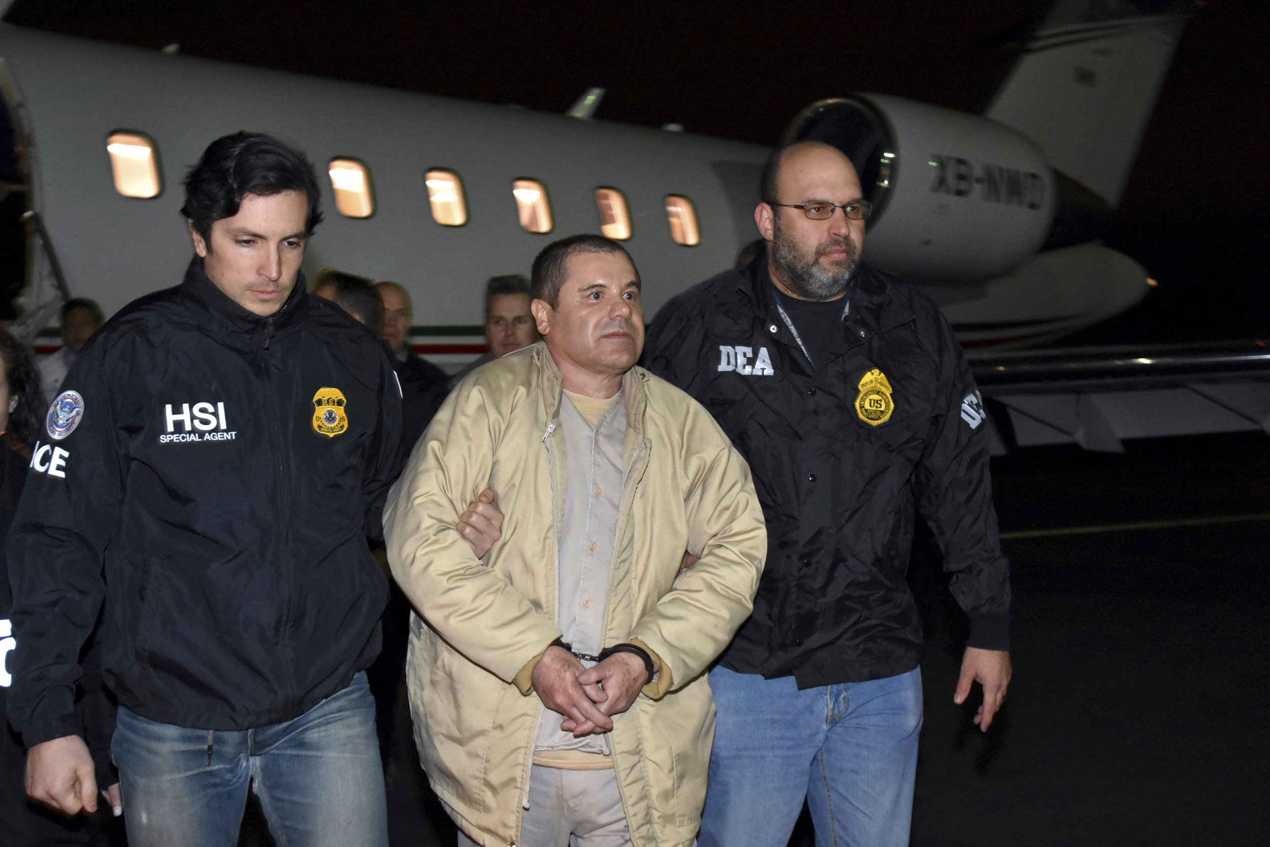 """U.S. agents escort Joaquin """"El Chapo"""" Guzman, center, from a plane to a waiting caravan of SUVs at Long Island MacArthur Airport, in Ronkonkoma, N.Y. in 2017. AP File Photo."""