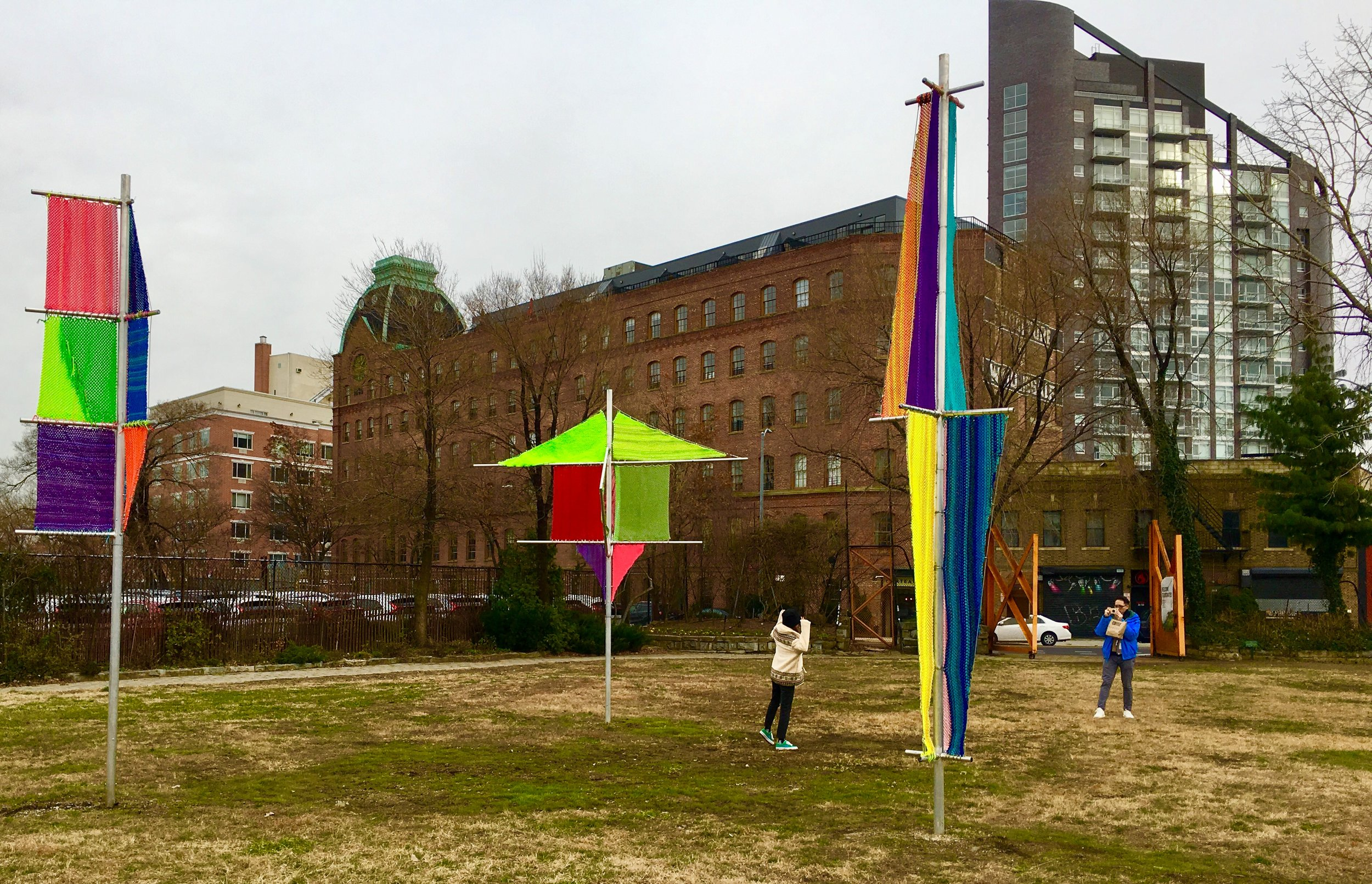 "A Socrates Sculpture Park visitor poses for a picture beside Jesse Harrod's work ""Flagging 1, 2, 3."""