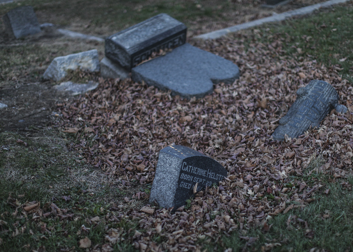 Sunken gravestone and toppled monuments fill All Faiths Cemetery in Middle Village.  Eagle  photos by Byron Smith.