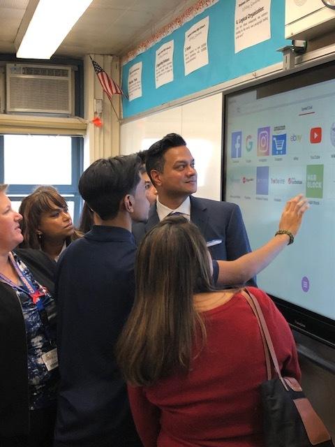 Subraj Foundation Director Tony Subraj looks on as students demonstrate the new Promethean board at Benjamin Cardozo High School.