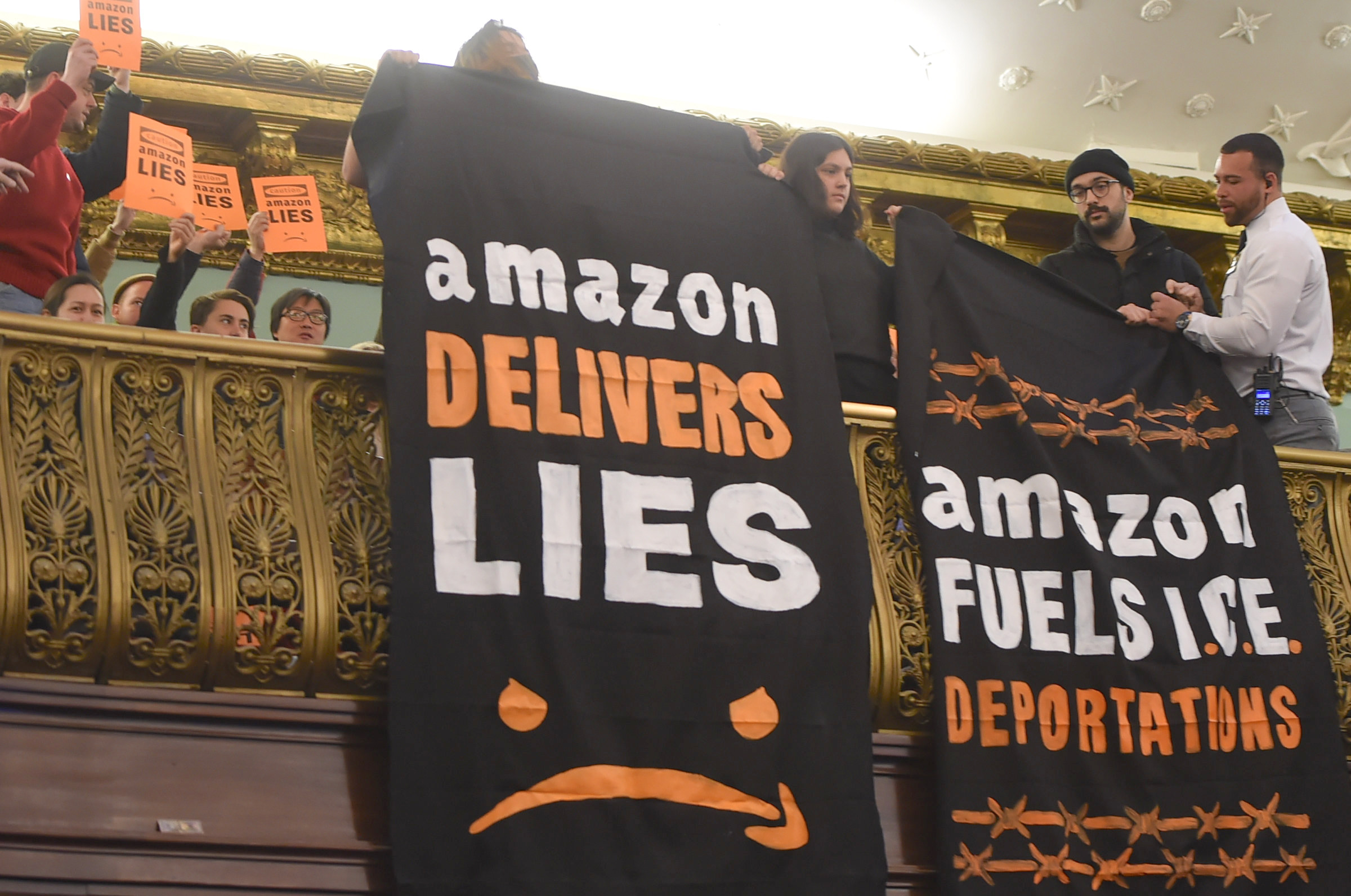Protesters in front row of the City Council chamber display their disdain for the Amazon deal.  Eagle  photos by Todd Maisel.
