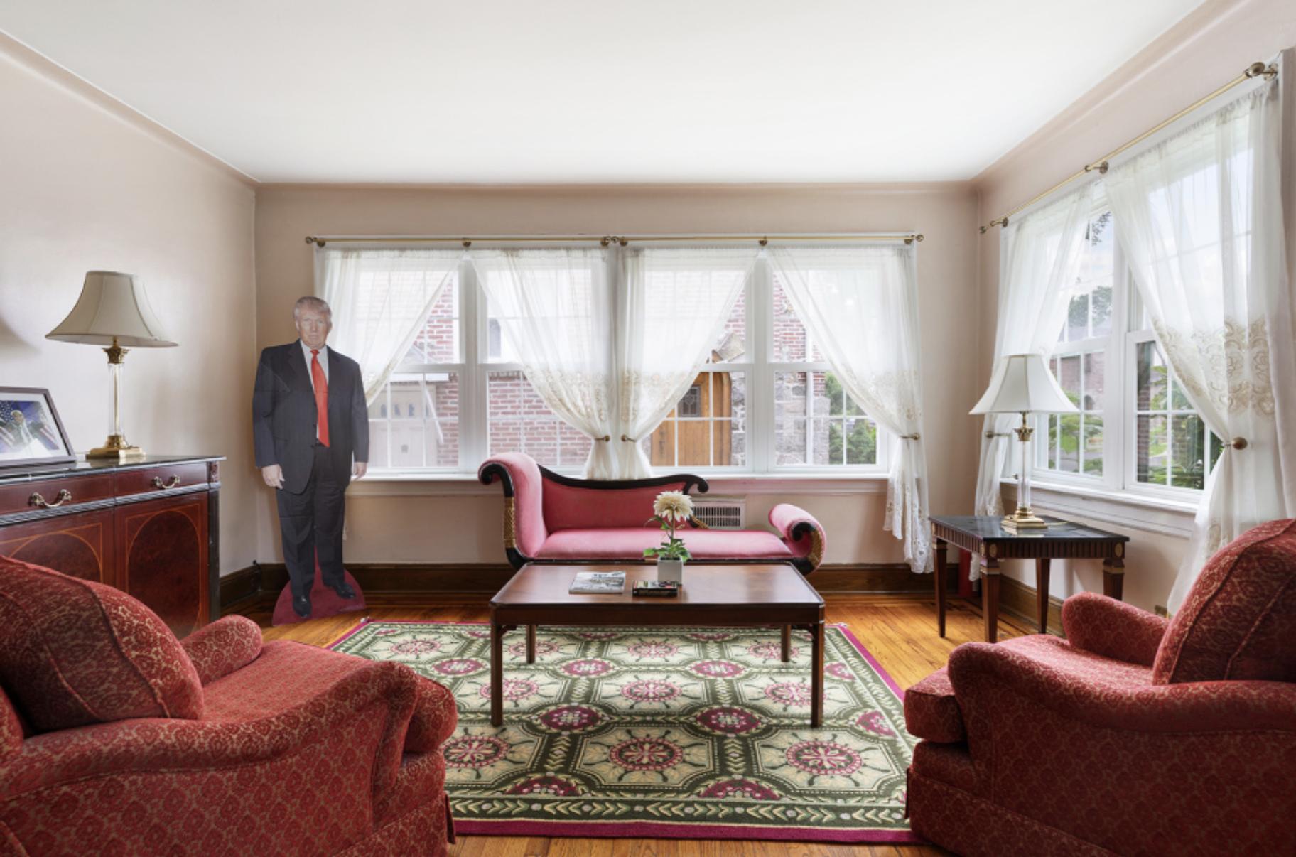 A cardboard cutout of Trump stands near the living room window. Photo via Compass.
