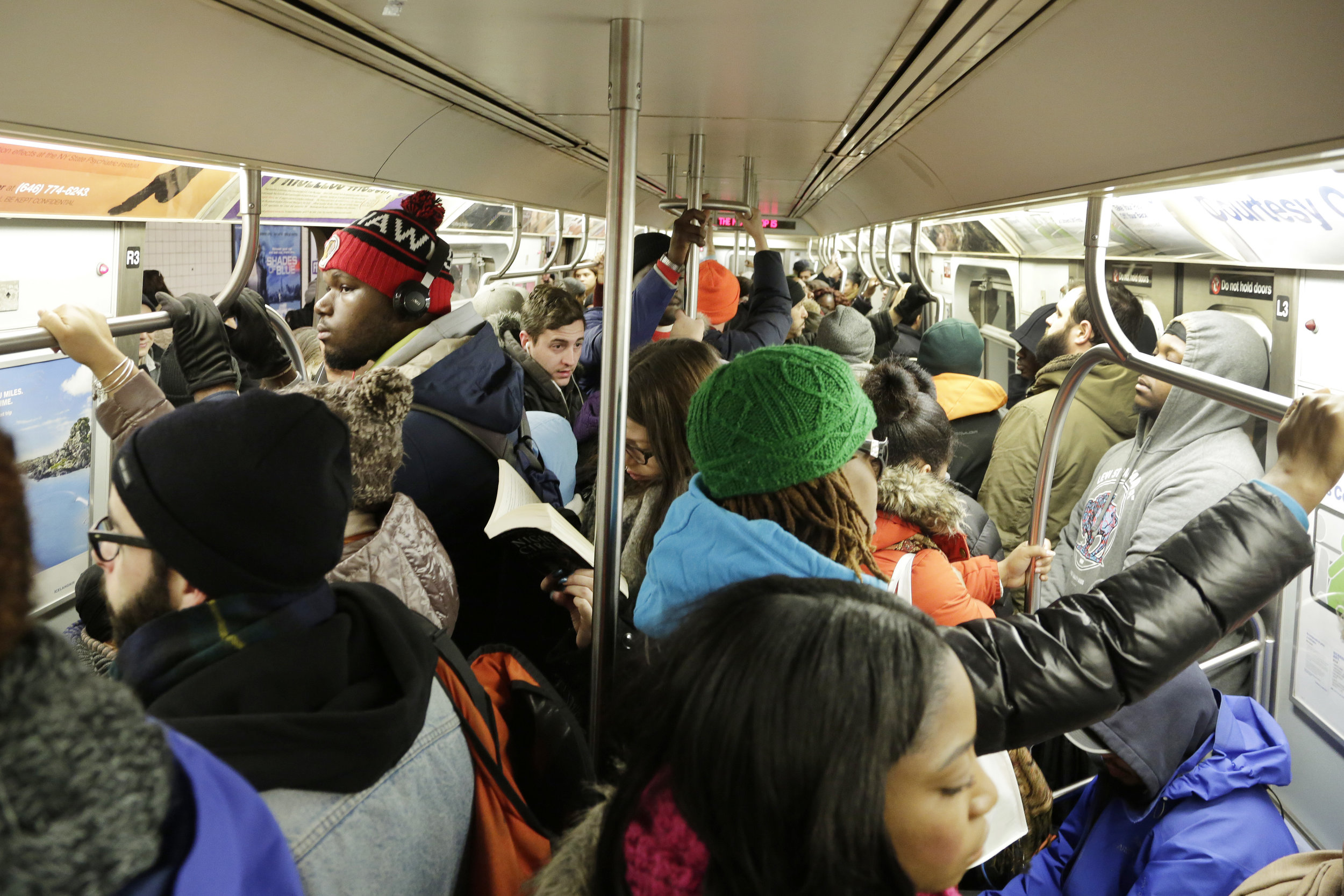 Commuters cram into a crowded subway car. AP Photo.